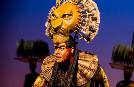 "Gerald Ramsey sports the Mufasa mask during a staging of ""The Lion King."" The touring production features 230 puppets, including the large masks worn by a handful of lead characters."