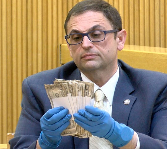 Monmouth County Prosecutors office Detective Nicholas Cattelona holds some of the $25,250 in cash that was found in Sarah Stern's safe deposit box in State Superior Court in Freehold Tuesday, February 5, 2019.  Liam McAtasney is on trial for the murder of Sarah Stern.