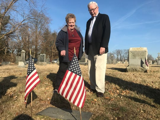 Muriel Smith, left, and Glenn Cashion visit Thomas T. Fallon's grave site at St. Rose of Lima Cemetery. The stone mentions Fallon's Medal of Honor.