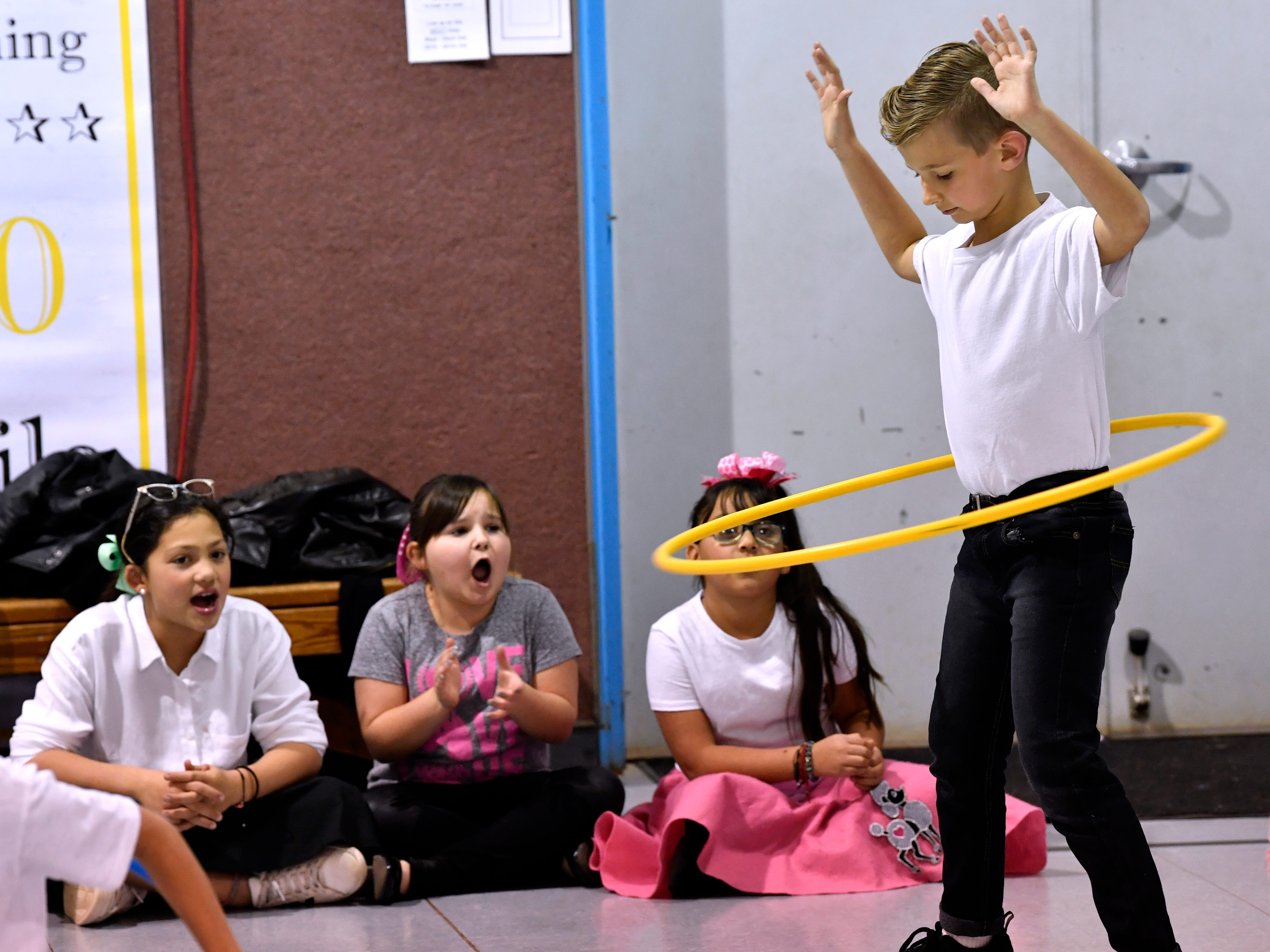 Elijah Palmer gets encouragement from other third-graders during a hula hoop contest in the Austin Elementary School gymnasium Jan. 25, 2019. Students from all grades participated in games and dances during Fifties Day.