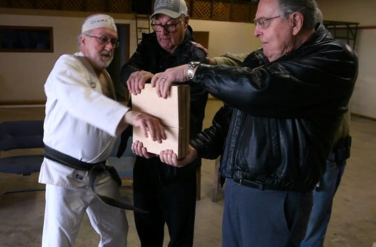 Kirby Krupa warms up by breaking three boards held by Harry Hubbard (center), Frank Healer and Mike Herd (unseen).