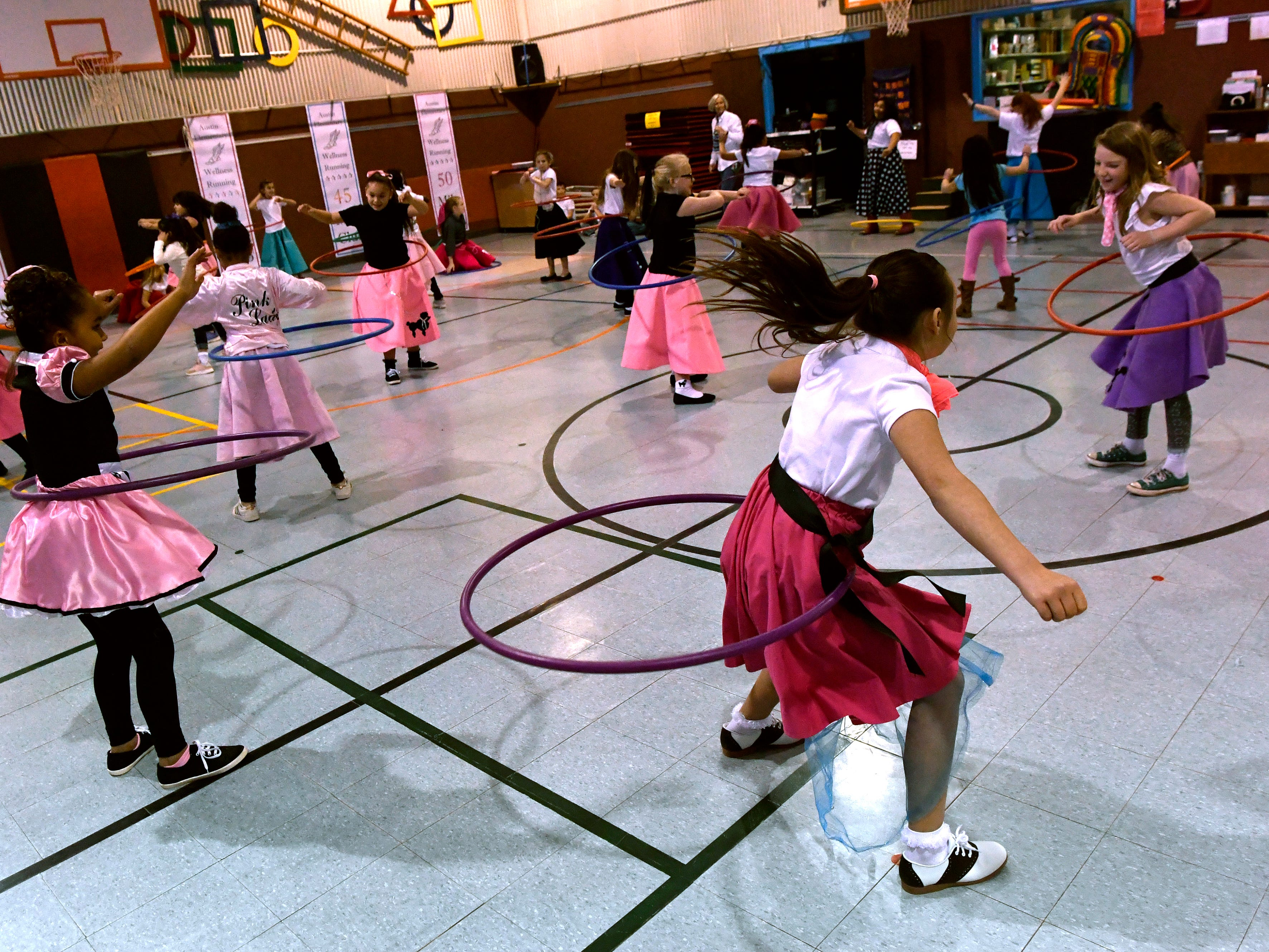Third grade girls hula hoop in the Austin Elementary School gymnasium Jan. 25, 2019 as part of Fifties Day. Students from all grades also performed the Twist, the Stroll, and the Hand Jive for family and friends.