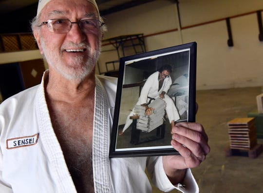 Kirby Krupa has held a black belt in karate since about 1979. Holding a photograph of him breaking seven concrete bricks when he was 40, Krupa attempted a similar feat Tuesday with cedar boards. He turned 80 on Jan. 25, but waited until the weather warmed a little to attempt the breaking in his Potosi workshop.