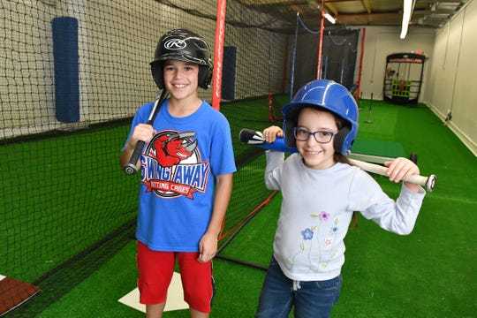 Deklyn Tynan, 10, and sister Bailey, 9, at the all new Swing Away Batting Cages, located at 600 E. John Rodes Blvd. in Melbourne. The grand opening is Feb. 9. The 7,500 square foot indoor facility is fully air conditioned, and includes batting cages, pitching mounds and a lounge.
