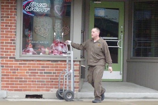 A UPS driver finishes making a delivery in downtown Bucyrus on Tuesday afternoon. While the temperatures in the upper 30s was shirt-sleeve weather for some, most pedestrians chose to wear coats. Warmer weather is expected to return today and Thursday, according  to the National Weather Service, with highs in the 50s. The catch? Expect rain both days.