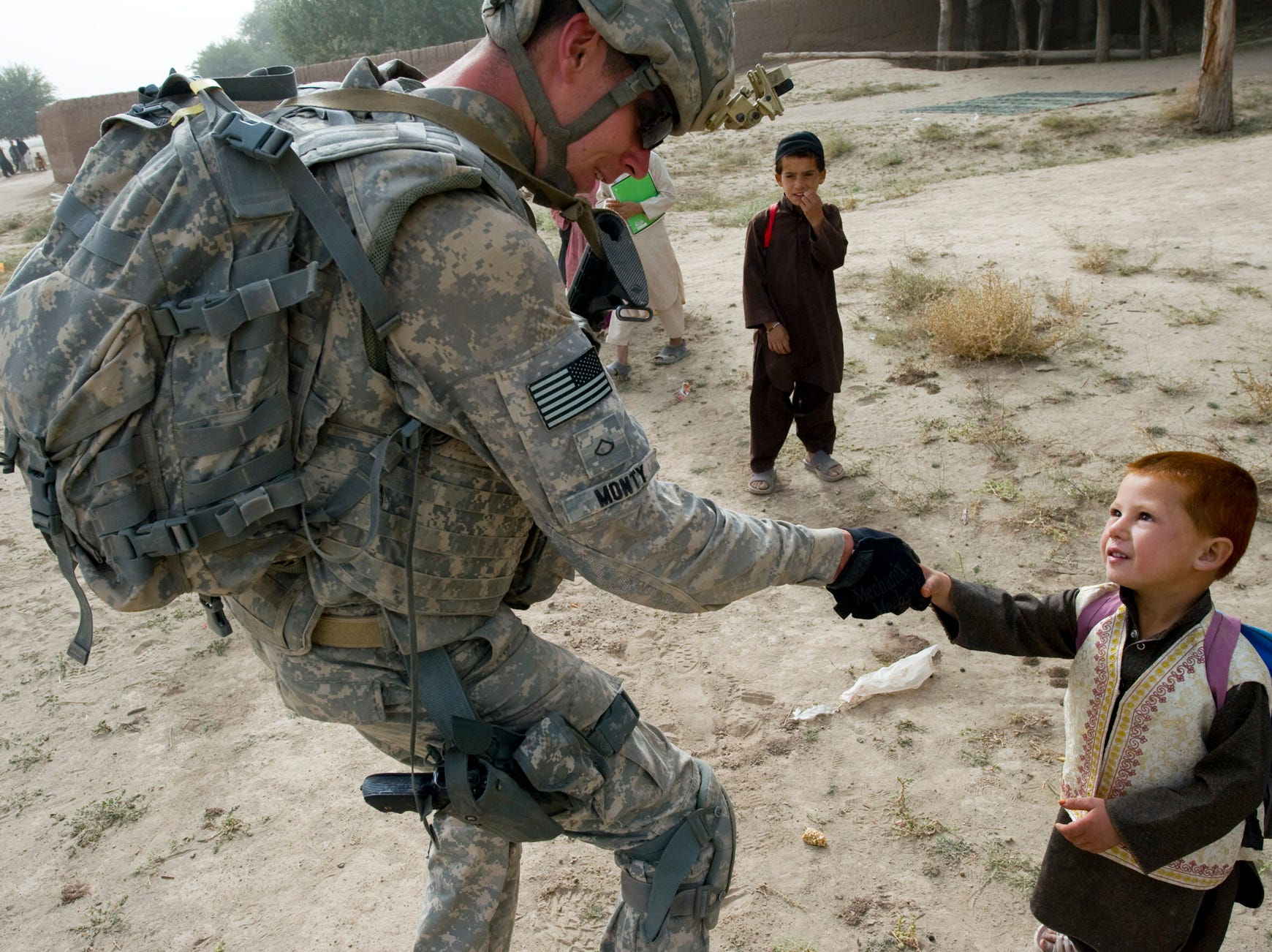 Vermont Guardsman William Monty, II, of Alstead, N.H., shakes hands with Afghans kids as he hands out candy, school supplies and bottled water during a patrol by the 3rd Platoon of Delta Company in the village of Rahman Keyhl in southern Paktia Province on Wednesday, September 15, 2010. Despite being well within Taliban country, kids greeted soldiers, a good sign that village leaders at least tolerated the U.S. presence there.