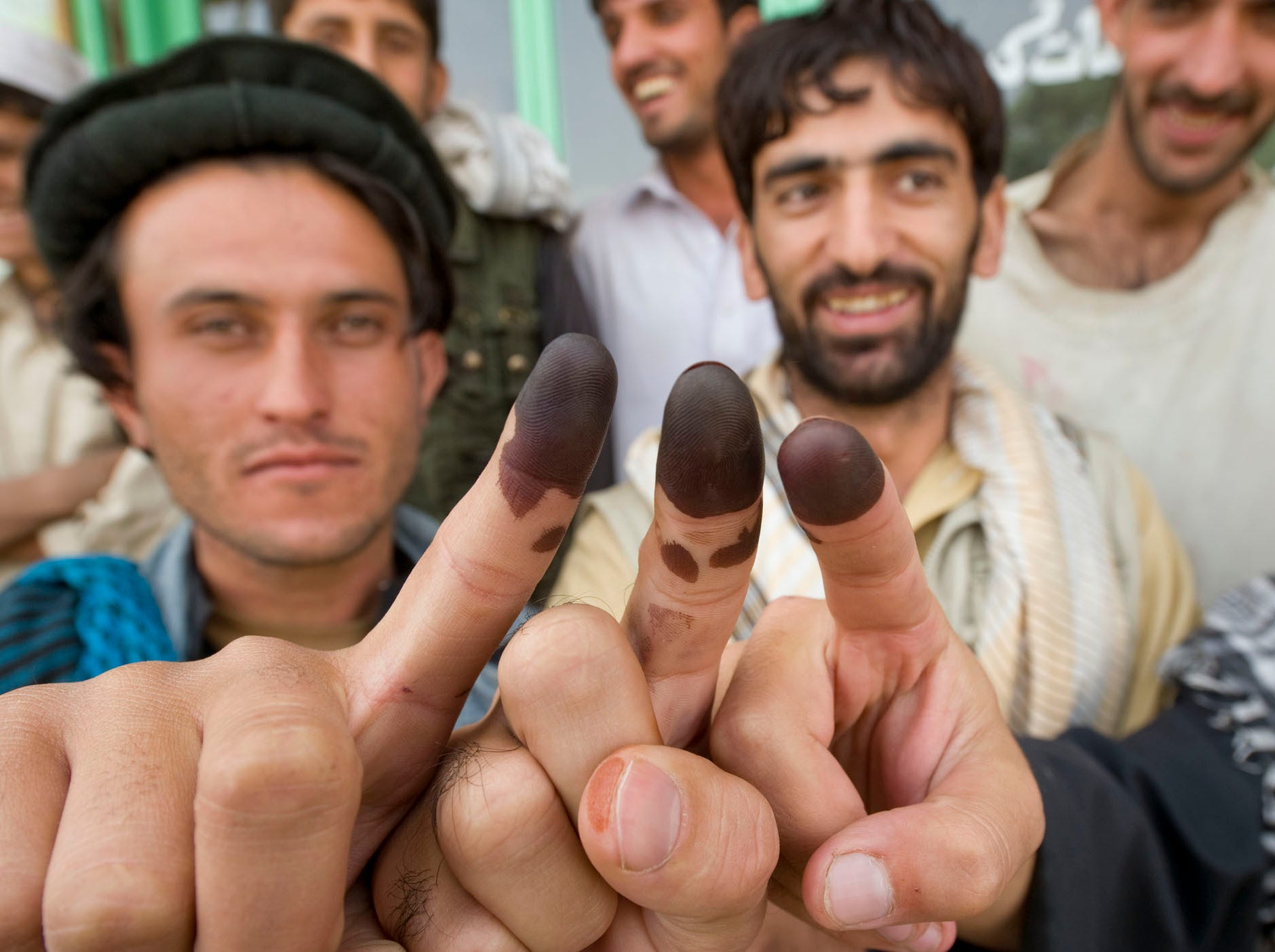 "From left, Safi Ullah Faqery holds up his finger along with Shams Nimatulluh and others after they all voted in Afghanistan's national elections on Saturday, September 18, 2010, in Gardez City in Paktia Province. ""I will tell you I am very very happy because I get to vote for who I like,"" said Faqery."