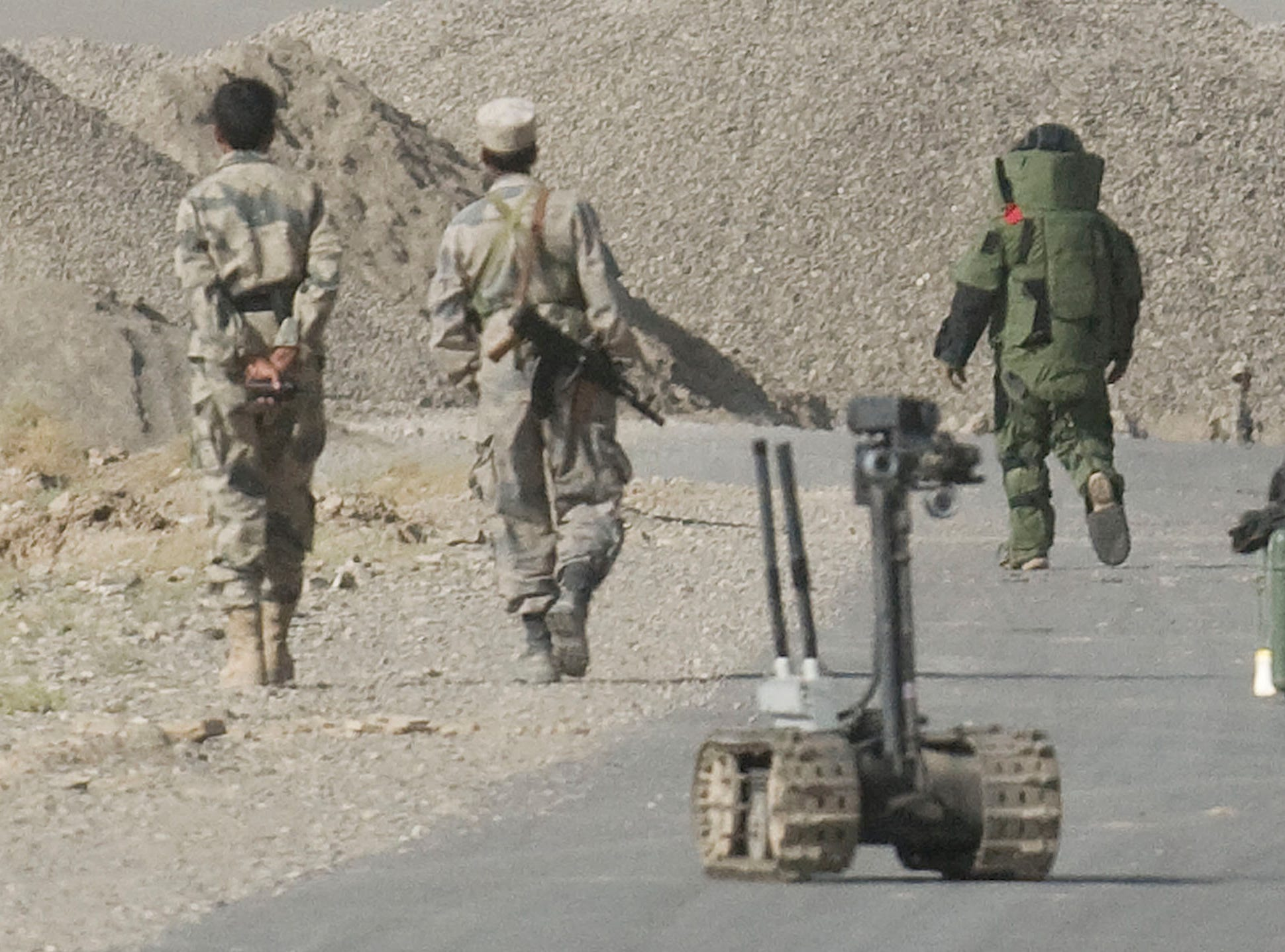 "An Explosive Ordinance Demolition bomb expert wearing a protective suit approaches a suspected IED on the road to Chamkani north of Gardez City on Sunday, September 19, 2010. The road was the site of at least one ""complex attack"" by insurgents recently combining IED, mortar or rocket and small arms fire."