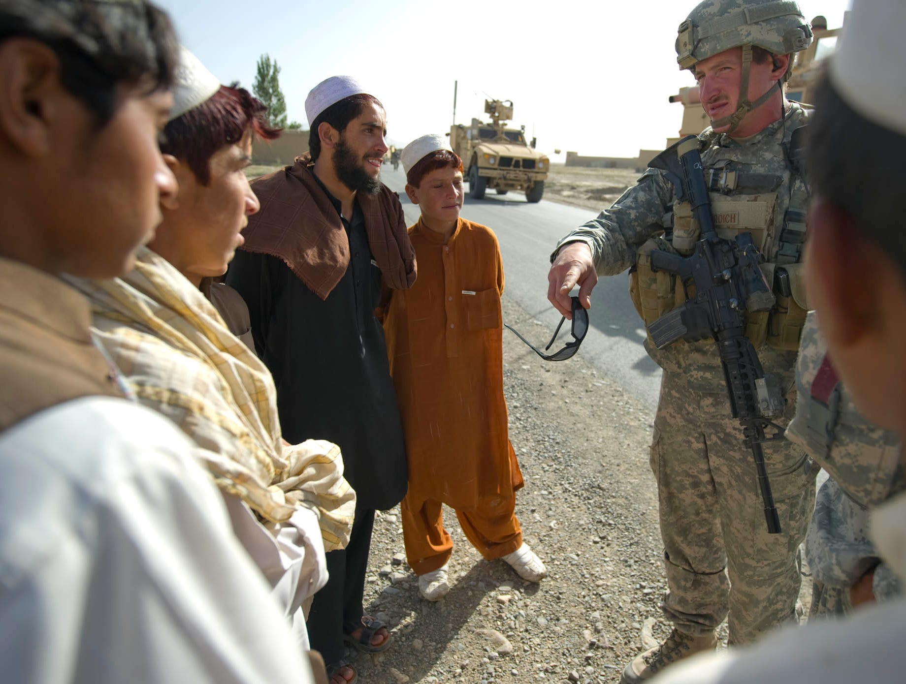 "Vermont National Guard Sgt. 1st Class Matt Briosch of St. Albans, Vt., warns kids along a road north of Gardez City to inform Afghan authorities if they see anything suspicious as EOD soldiers sweep the road looking for reported IED activity on Sunday, September 19, 2010. The road was the site of at least one ""complex attack"" by insurgents recently combining IED, mortar or rocket and small arms fire."