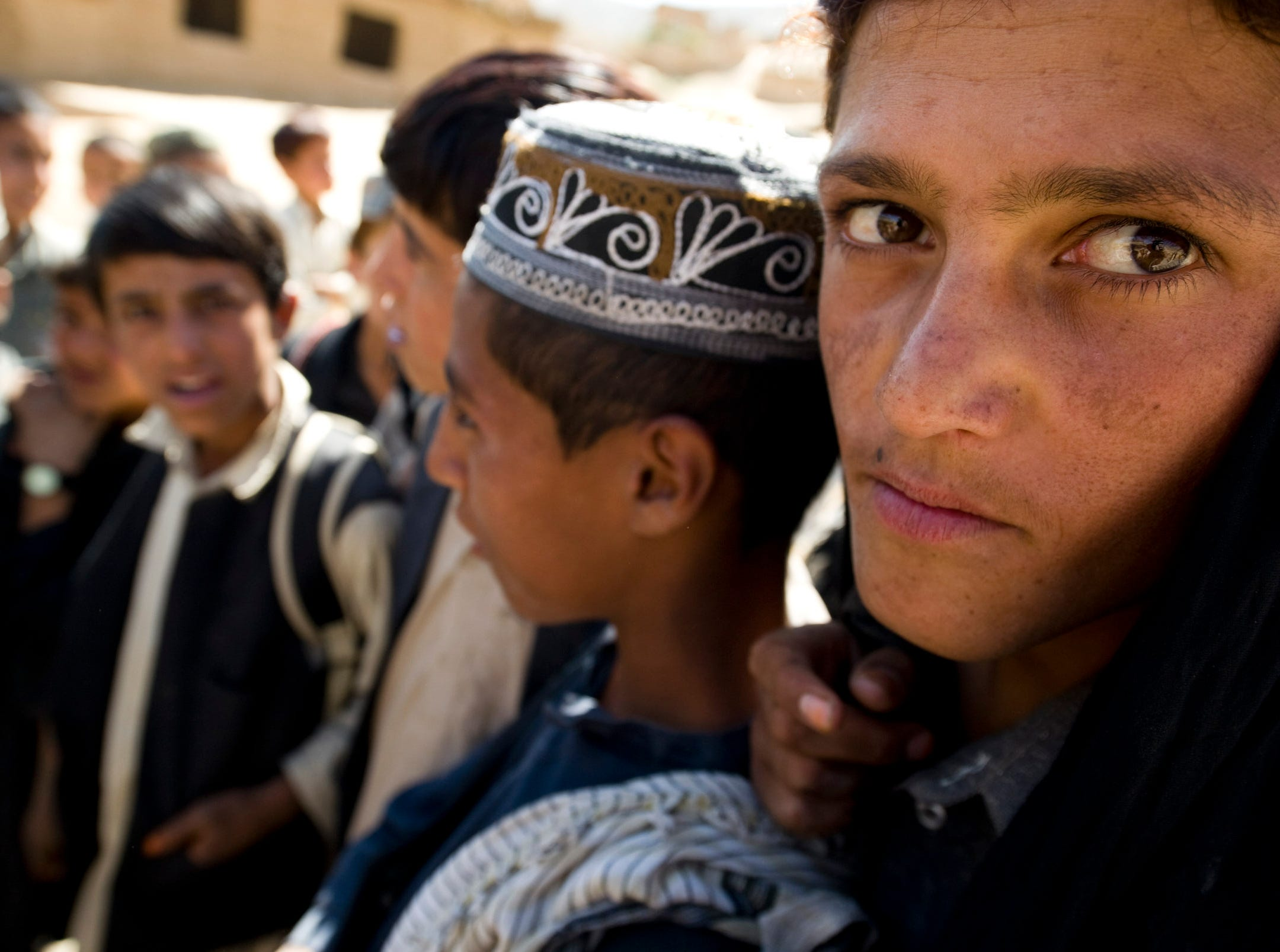 Afghan boys crowd around a Vermont National Guard soldier for an impromptu English lesson at Shawo Kelay, a small village in the mountains of Parwan Province northeast of Kabul on Thursday, September 23, 2010.
