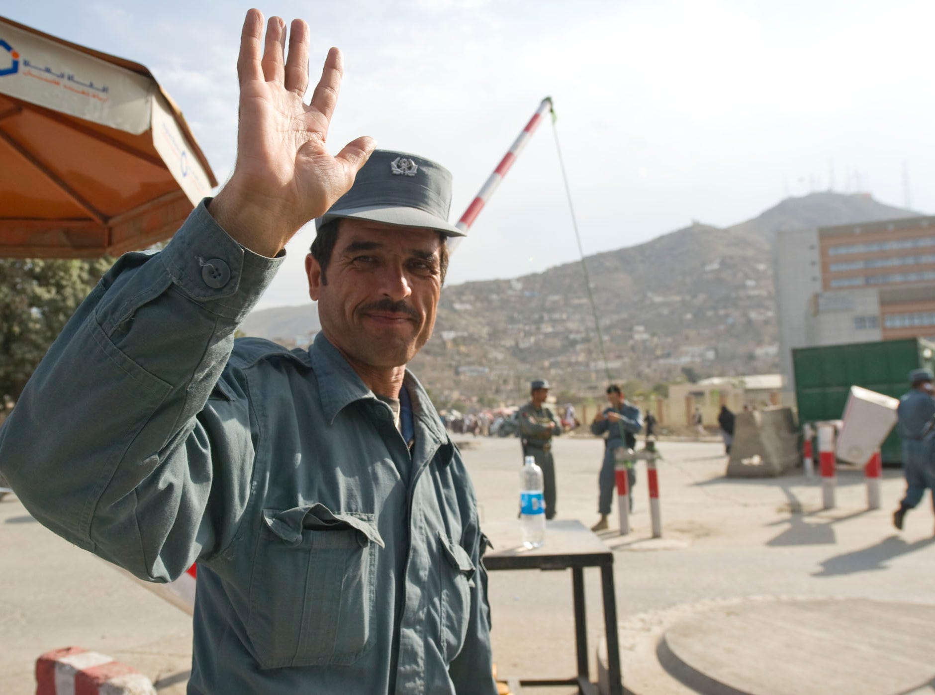 An Afghan Uniform Police officer waves from his checkpoint in downtown Kabul on Tuesday, September 28, 2010. Only a few years ago, Afghans who traveled these roads at night were often shot at or worse, but the number of incidents has declined as more police and Afghan National Army soldiers are trained.