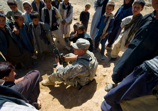 Vermont National Guard Spc. Matt Tardiff of Boston, Mass., is surrounded by curious Afghan kids looking for pens, notebooks or candy, things that are hard to come by in the remote village of at Shawo Kelay. Kids friendly to U.S. forces is a first sign of minimal Taliban influence. In another village just over the mountains, soldiers received a very different reception when kids threw rocks at their patrol.