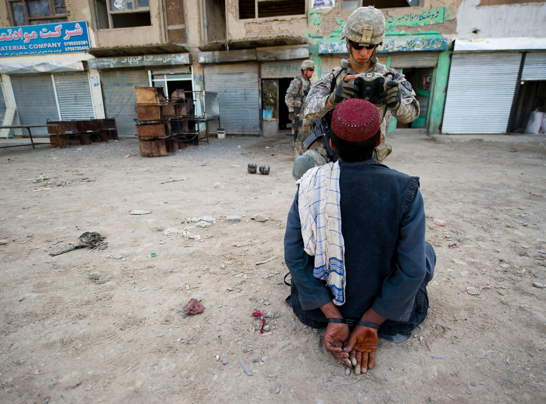 A member of the 615th Military Police Company processes an Afghan's information into a HIIDE  (Handheld Interagency Identity Detection Equipment) during a raid of a suspected weapons and IED stash at a building in downtown Gardez in Paktia Province, Afghanistan, on Friday morning, September 17, 2010. No weapons or bomb-making materials were found and all the people detained were later released.