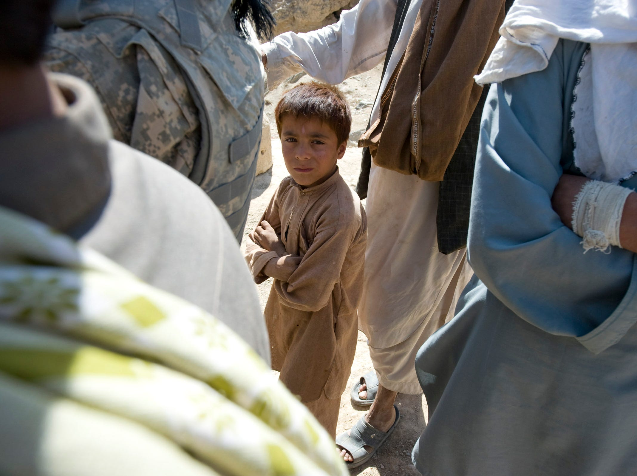 September 2010: An Afghan boy keeps his distance, not sure of what to make of a Vermont National Guard visit along with a U.S. Department of Agriculture representative in the remote village of Kariz Gha in the mountains of Parwan Province. Elders there complained that another U.S. aid worker visited months ago, made promises, but that no action came from the visit.