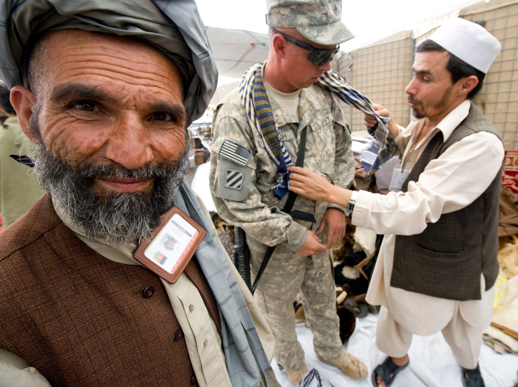 Left, Karimulla Sharif Fullah keeps a sharp eye out for new customers as Allah Mohammad tries to sell an Oklahoma Guardsman on a scarf on Monday, September 13, 2010, at a market set up at the edge of Forward Operating Base Gardez.