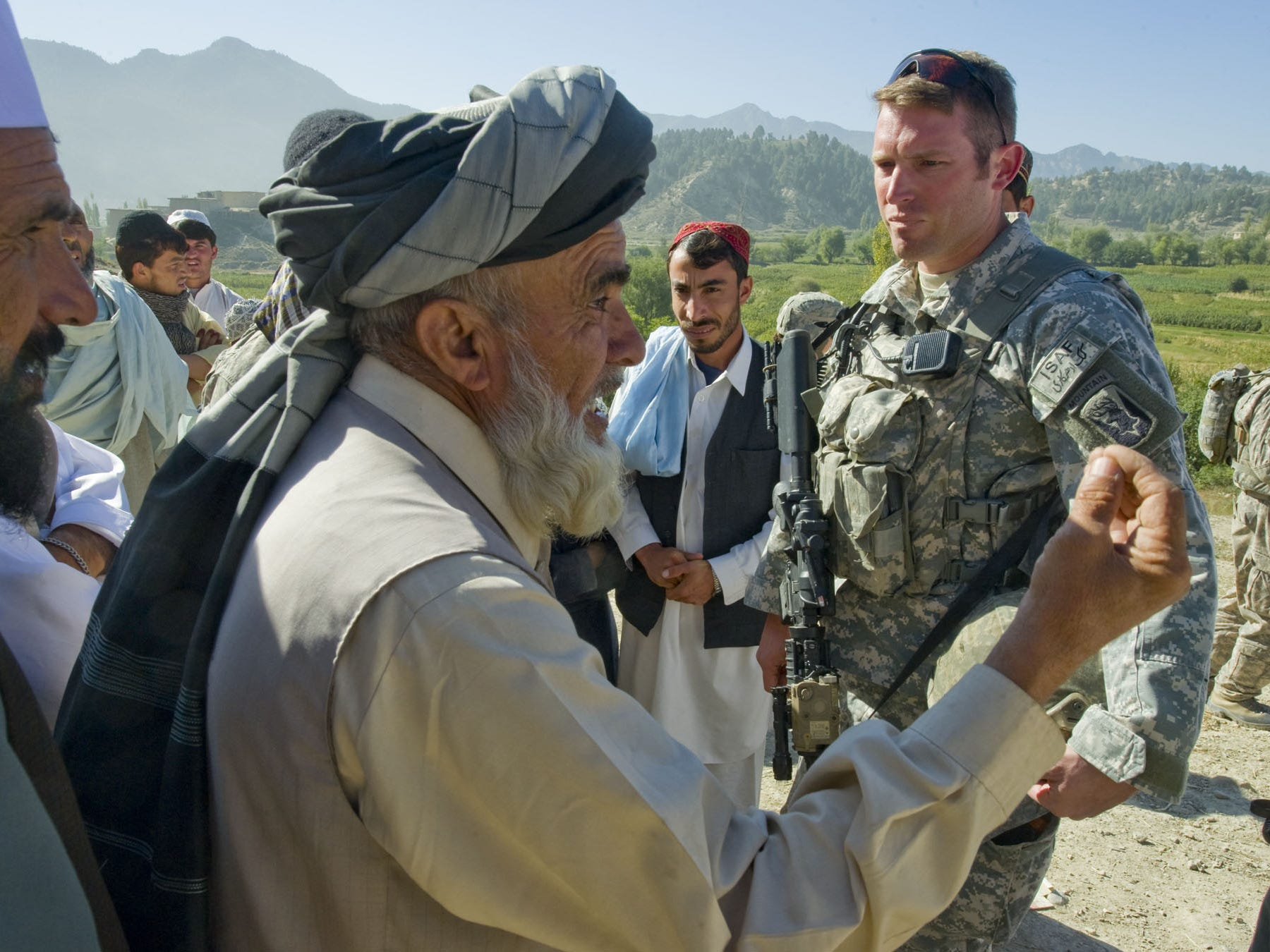 Right, Vermont National Guardsman Sgt. 1st Class Jay Pedro of Woodstock patiently listens to Malik Amanullah, a village elder in Kuzah Shegah, complain about the presence of soldiers there on Tuesday morning, September 21, 2010. Soldiers purposely arrive there unannounced looking for information about an insurgent spotter that was seen there as Combat Outpost Herrera was being attacked by mortar fire. Amanullah was upset there was no warning of the visit. But after Pedro patiently listened, and tolerated the elder's complaints in front of the village residents, the tone quickly changed and his men were invited to drink tea. Later, Pedro would comment that if he had not allowed the leader to demonstrate his authority in front of the soldiers and his people -- a sign of respect on the part of Vermont soldiers -- that the visit could have taken a turn for the worst.