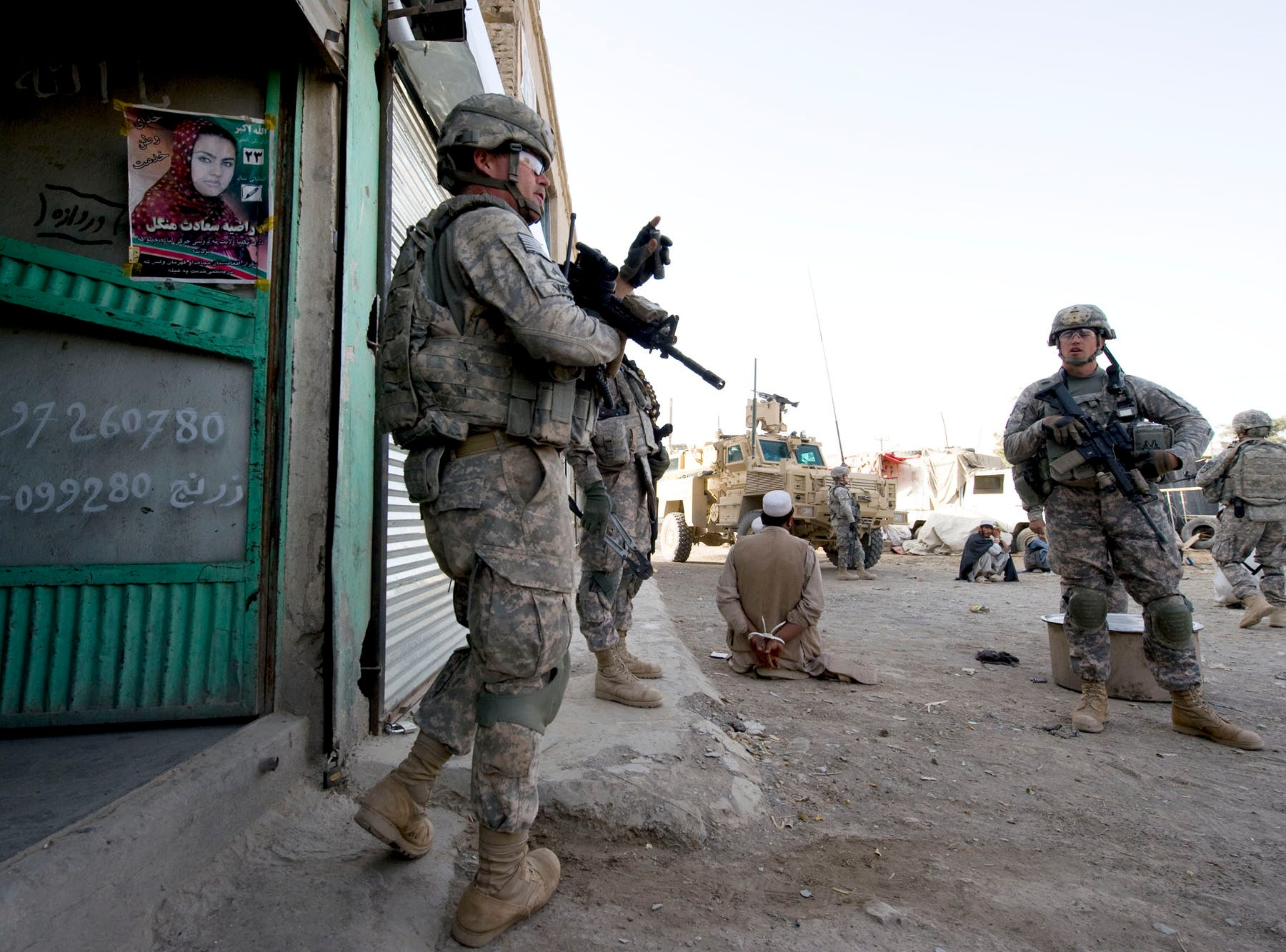 Center, Vermont National Guard Sgt. Donald Stocker of Delta Company emerges from a shop in downtown Gardez in Paktia province, Afghanistan, Friday morning, September 17, 2010, looking for suspected IED and weapons caches. The early-morning raid was delayed several hours after local Afghan police failed to show up on time, leading some soldiers to question weather insurgents were tipped off before the raid.