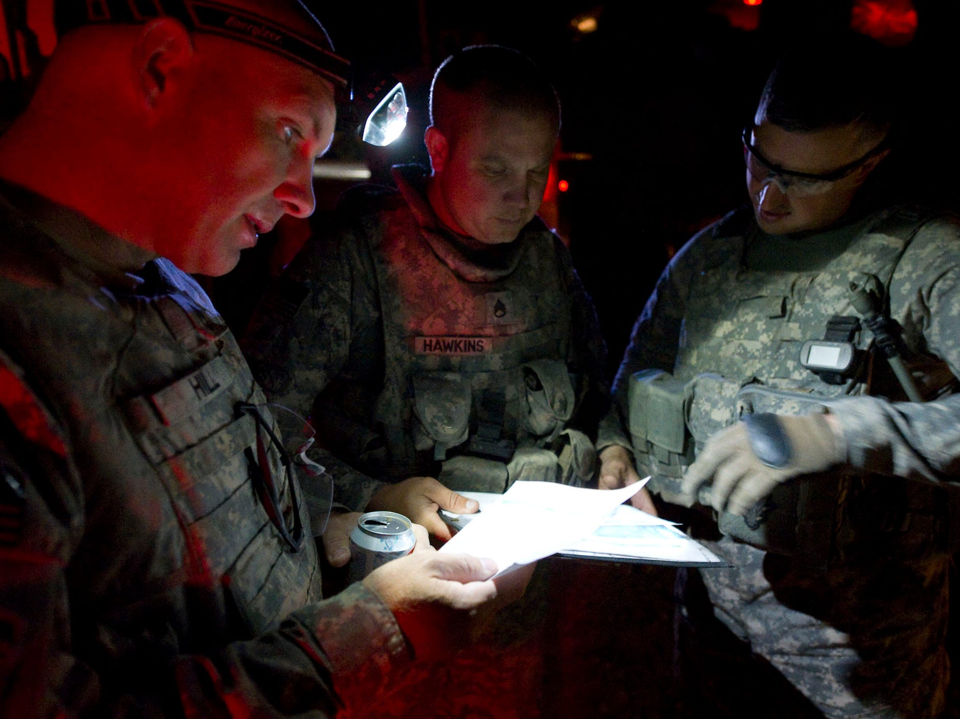 From left, Vermont National Guard Sgt. 1st Class Matthew Hill of St. Albans, Vt., Staff Sgt. Scott Hawkins of East Montpelier, Vt., and 1st Sgt. Eric Duncan of Northfield, Vt., go over plans to raid a suspected weapons and IED cache early Friday morning, September 17, 2010, at Forward Operating Base Gardez in Paktia Province. The raid was delayed after Afghan Uniformed Police postponed the operation saying they had no units available due to election preparations.