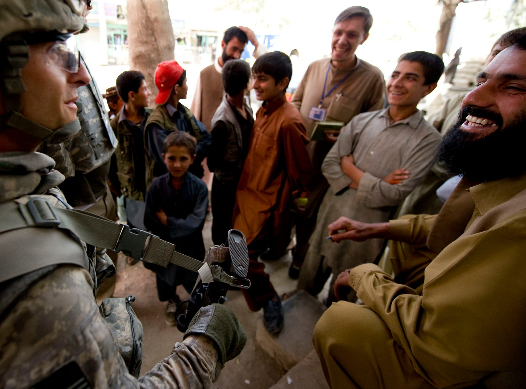 Vermont National Guard medic Sgt. Paul Jardine, 37, of Fair Haven, Vt., talks with a shopkeeper as kids gather around a security checkpoint to joke and talk to him during a raid of a suspected weapons and IED stash at a building in downtown Gardez in Paktia Province, Afghanistan, Friday morning, September 17, 2010.