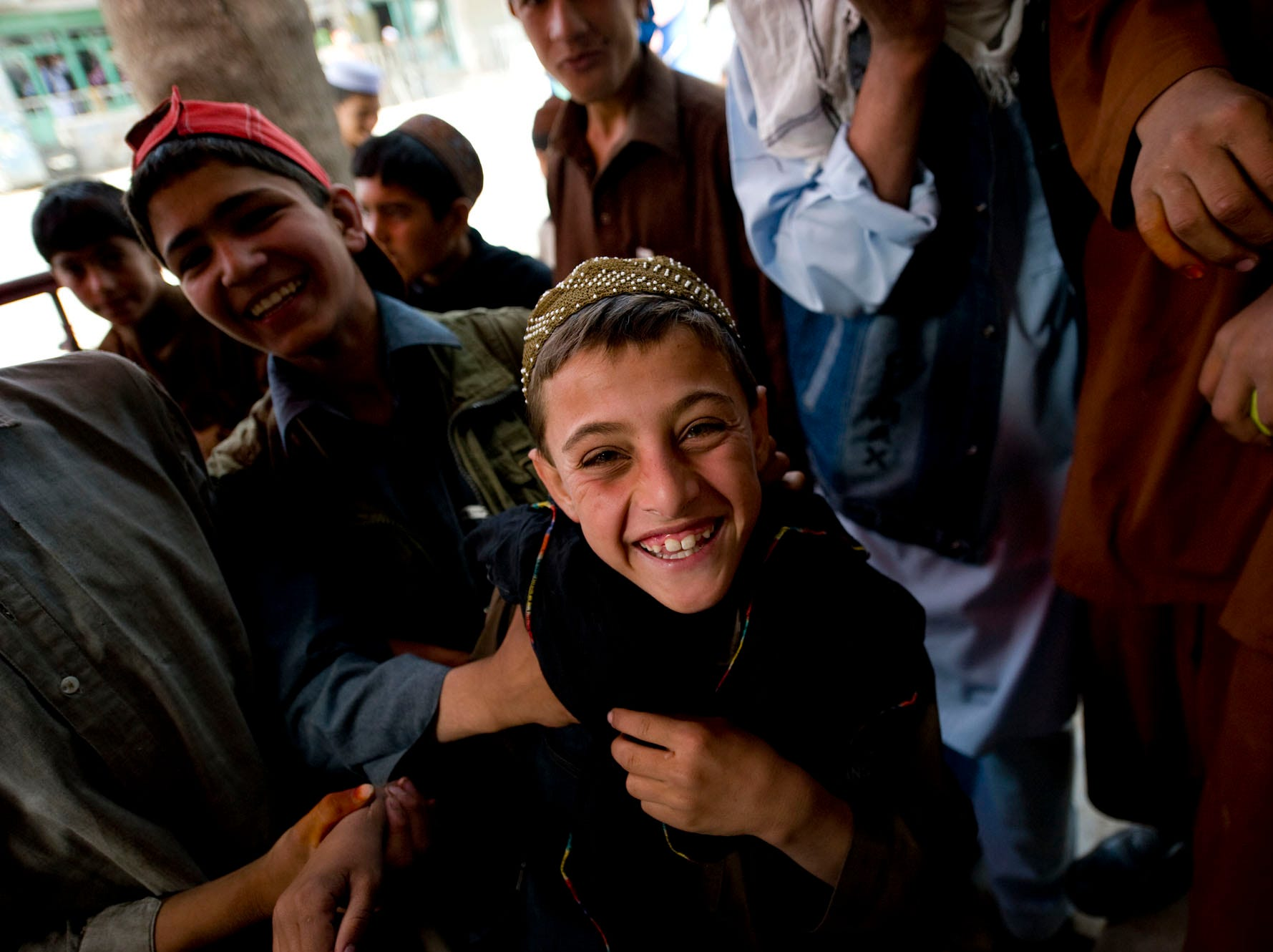 Kids gather around a security checkpoint to joke and talk with Vermont National Guard soldiers from Delta Company during a raid of a suspected weapons and IED stash at a building in downtown Gardez in Paktia Province, Afghanistan, on Friday morning, September 17, 2010.