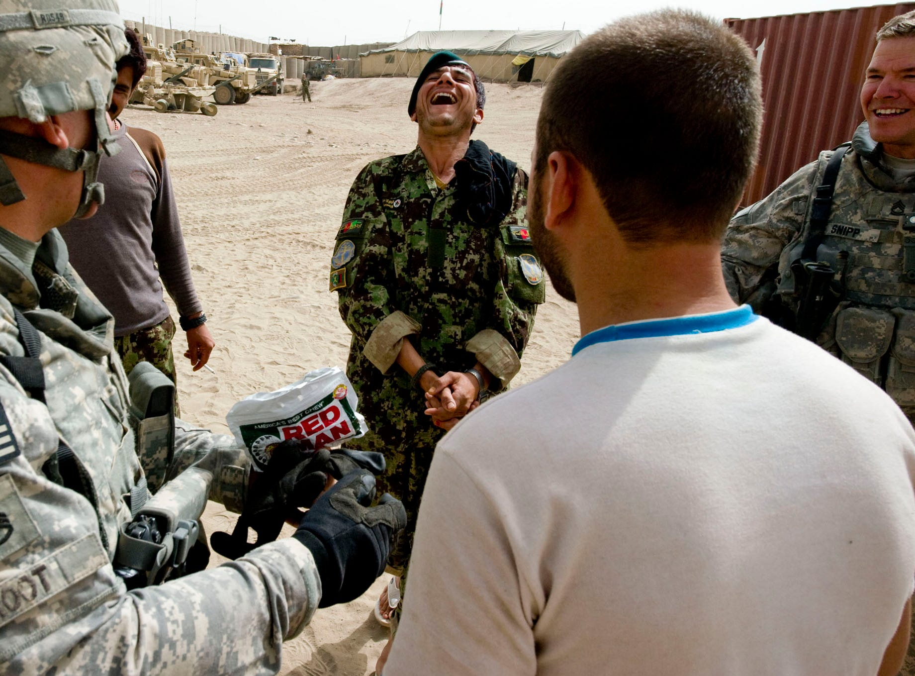 Left, Vermont National Guard Sgt. Carl Root of Milton offers some chewing tobacco to an Afghan National Army soldier with, right, Sgt. 1st Class Thomas Snipp of Morrisville after Echo Company arrived at a new Afghan Combat Post in Rahman Kheyl, a remote part of Afghanistan in southern Paktia Province, on Tuesday, September 14, 2010. The post, which is still under construction, is a joint effort of Vermont National Guard, Macedonian Rangers and the Afghan Army.