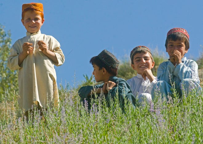 Afghan kids watch U.S. soldiers as they meet with village leaders in Kuzah Shegah during a patrol on Tuesday, September 21, 2010.