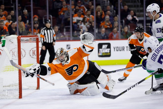 Carter Hart's diving save on Canucks forward Nikolay Goldobin helped seal the Flyers' 2,000th win in franchise history.