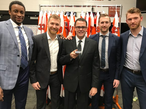 Wayne Simmonds, Claude Giroux, interim coach Scott Gordon, Andrew MacDonald and Sean Couturier pose with a puck commemorating the 2,000th win in Flyers history.
