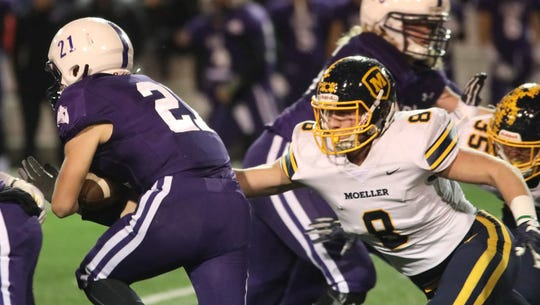 Moeller  defender Ryan Mullaney (8) chases  Elder running back  Joe Catania (21) during their    playoff game , Friday, Nov. 2, 2018.