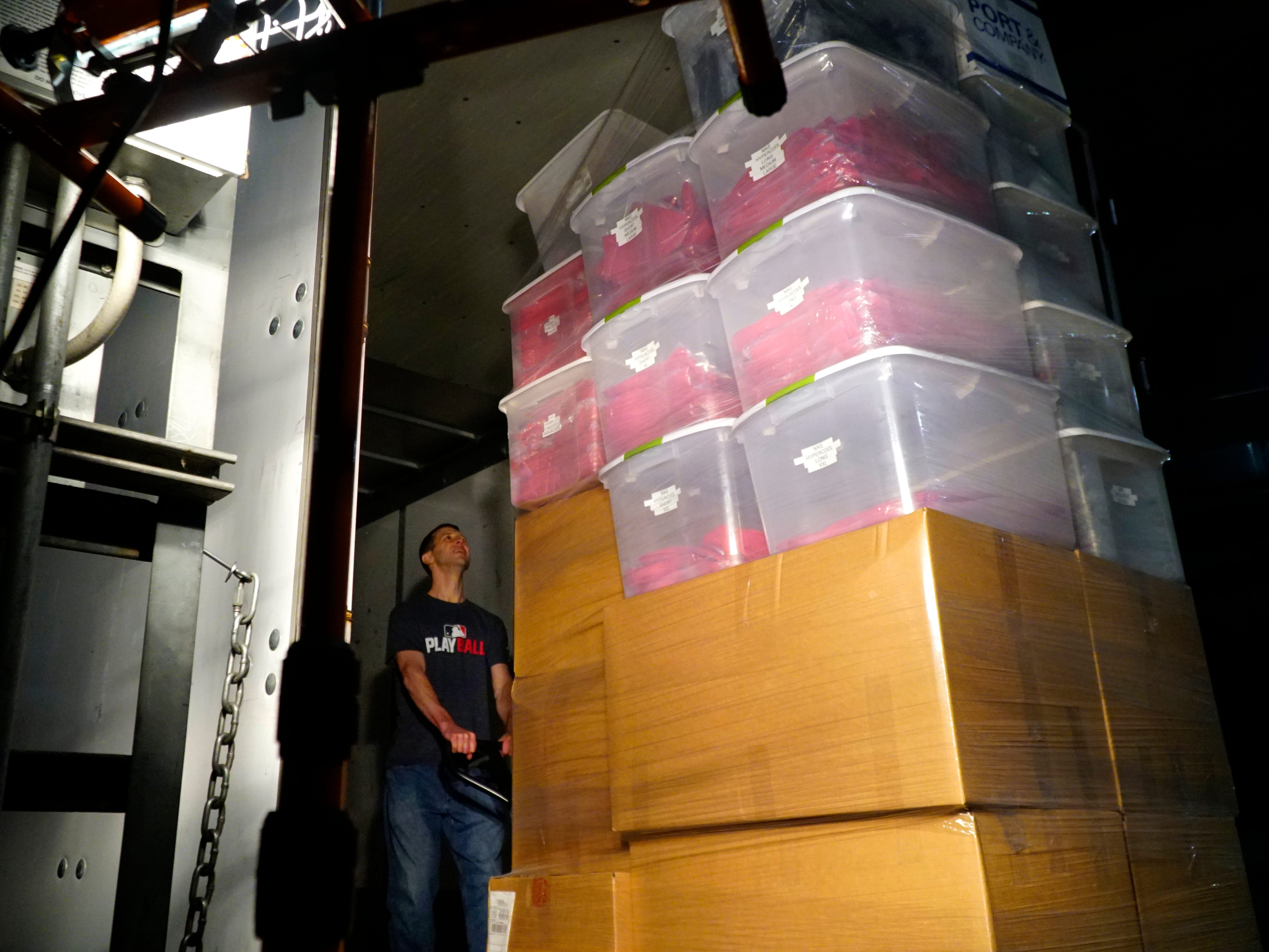 A staffer loads a tower of Cincinnati Reds apparel at at Great American Ball Park, Tuesday, Feb. 5, 2019. The team's tractor-trailer will haul 1,000 baseball bats, 500 hats, and 100 cases of sunflower seeds to the Reds Development Complex in Phoenix, Ariz.