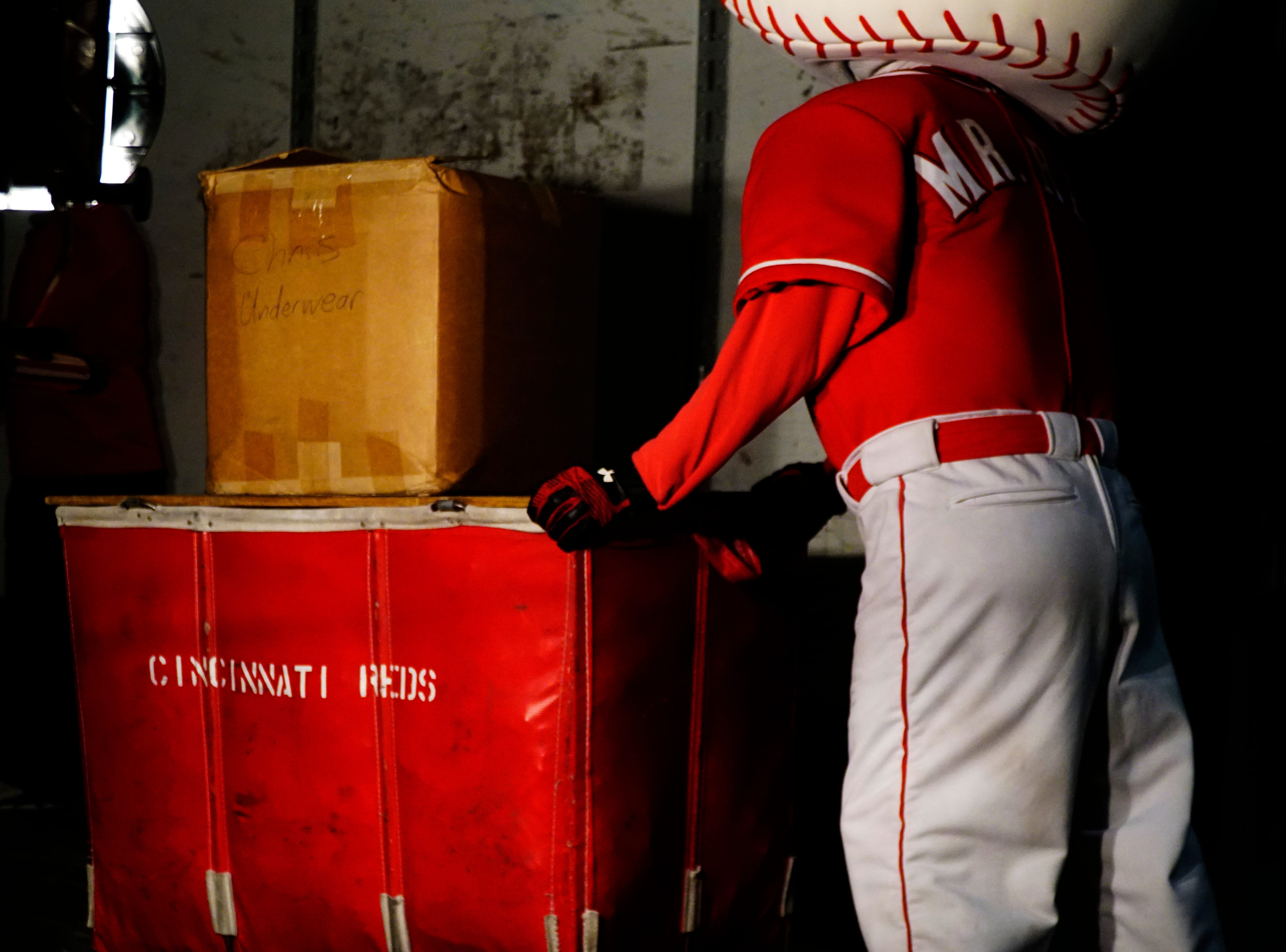 The Cincinnati Reds' mascot Mr. Red helps the team pack for Spring Training at Great American Ball Park, Tuesday, Feb. 5, 2019.