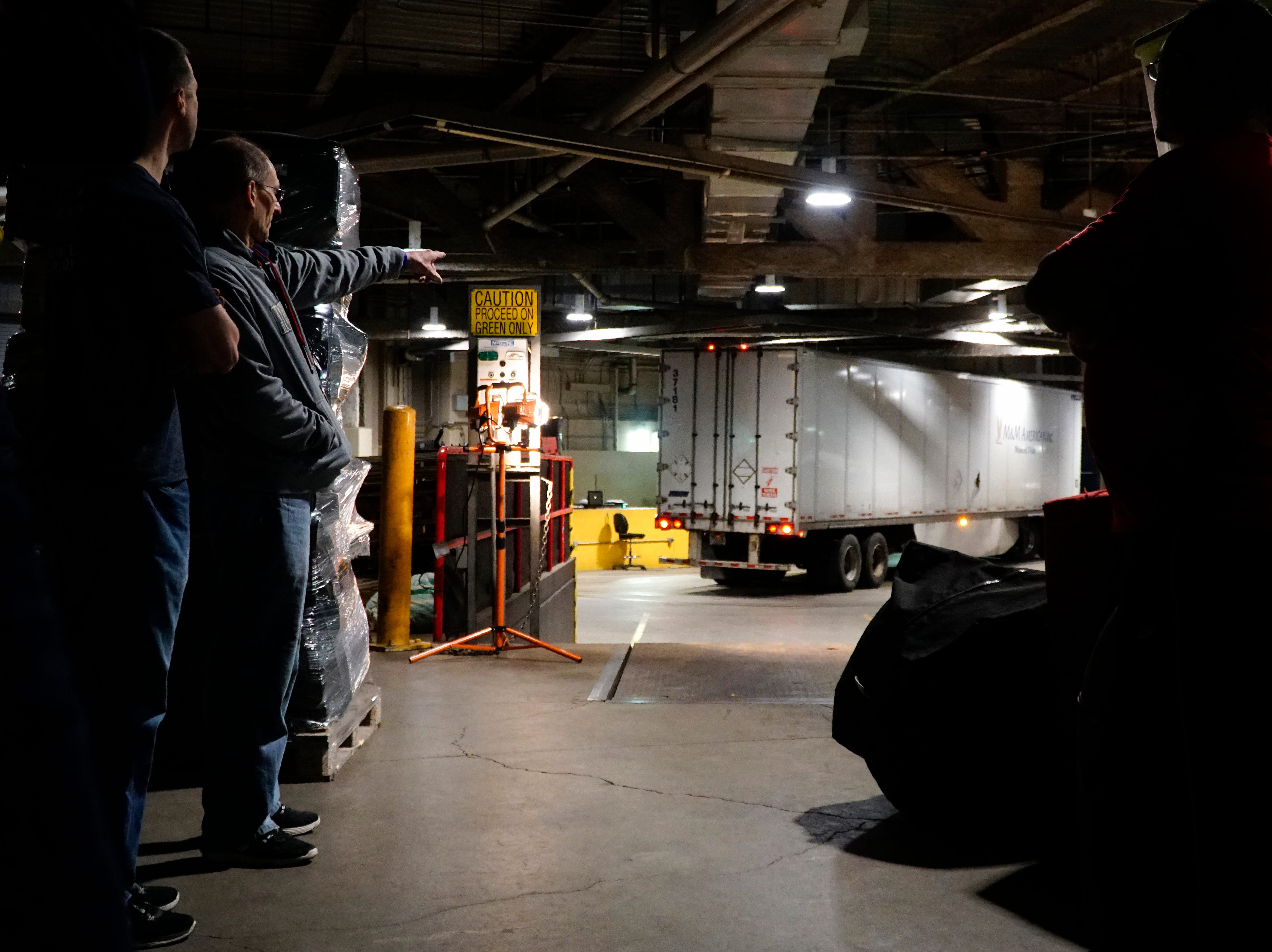 Workers wait for The Cincinnati Reds' tractor-trailer to back into the loading bay beneath Great American Ball Park, Tuesday, Feb. 5, 2019. After loading, the truck will travel 1,825 miles from Cincinnati to the Reds Development Complex in Phoenix, Ariz.