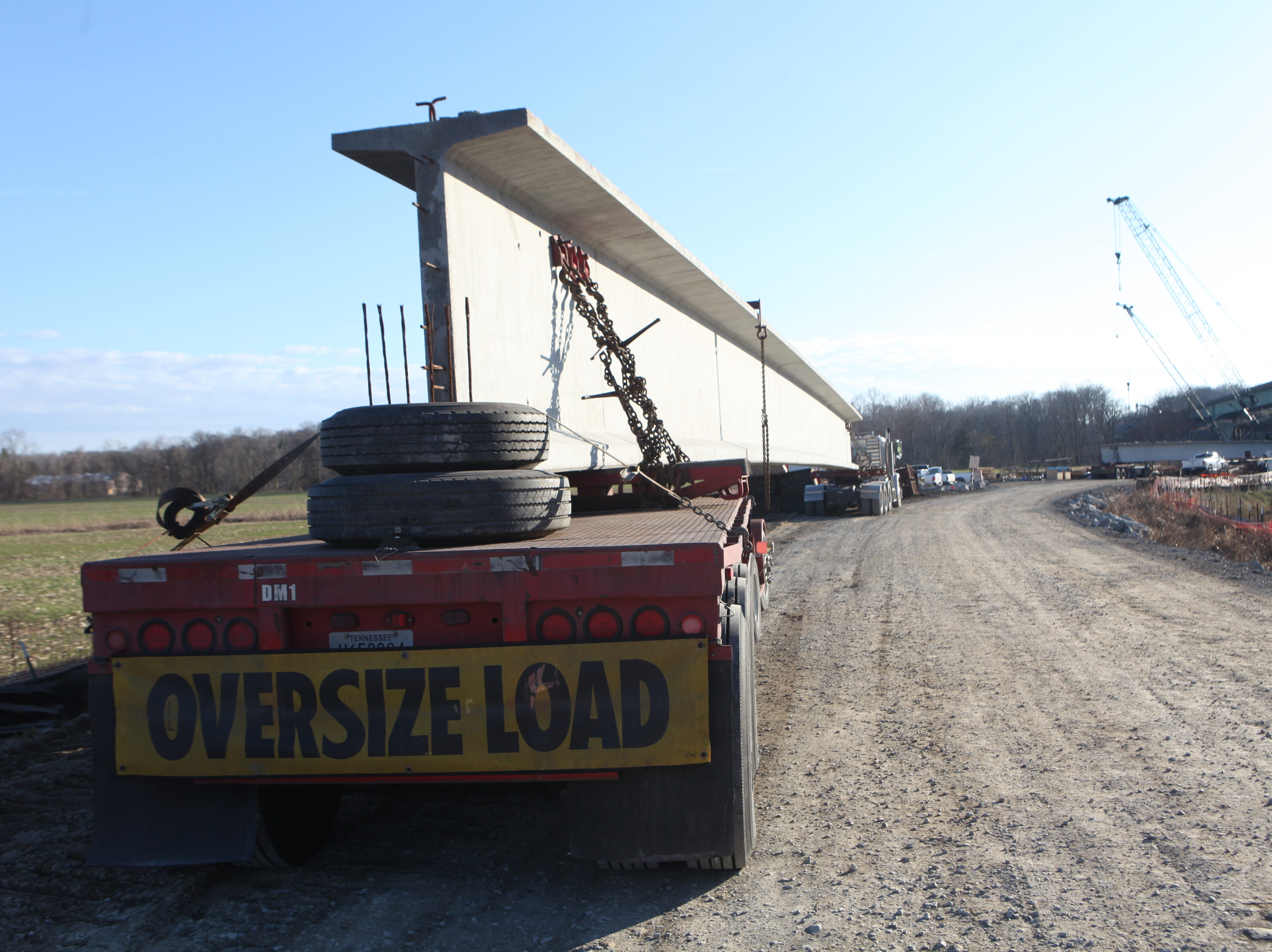 130-foot-long steel beams arrive and are prepared for installation at the McClure Bridge construction site in February 2019.