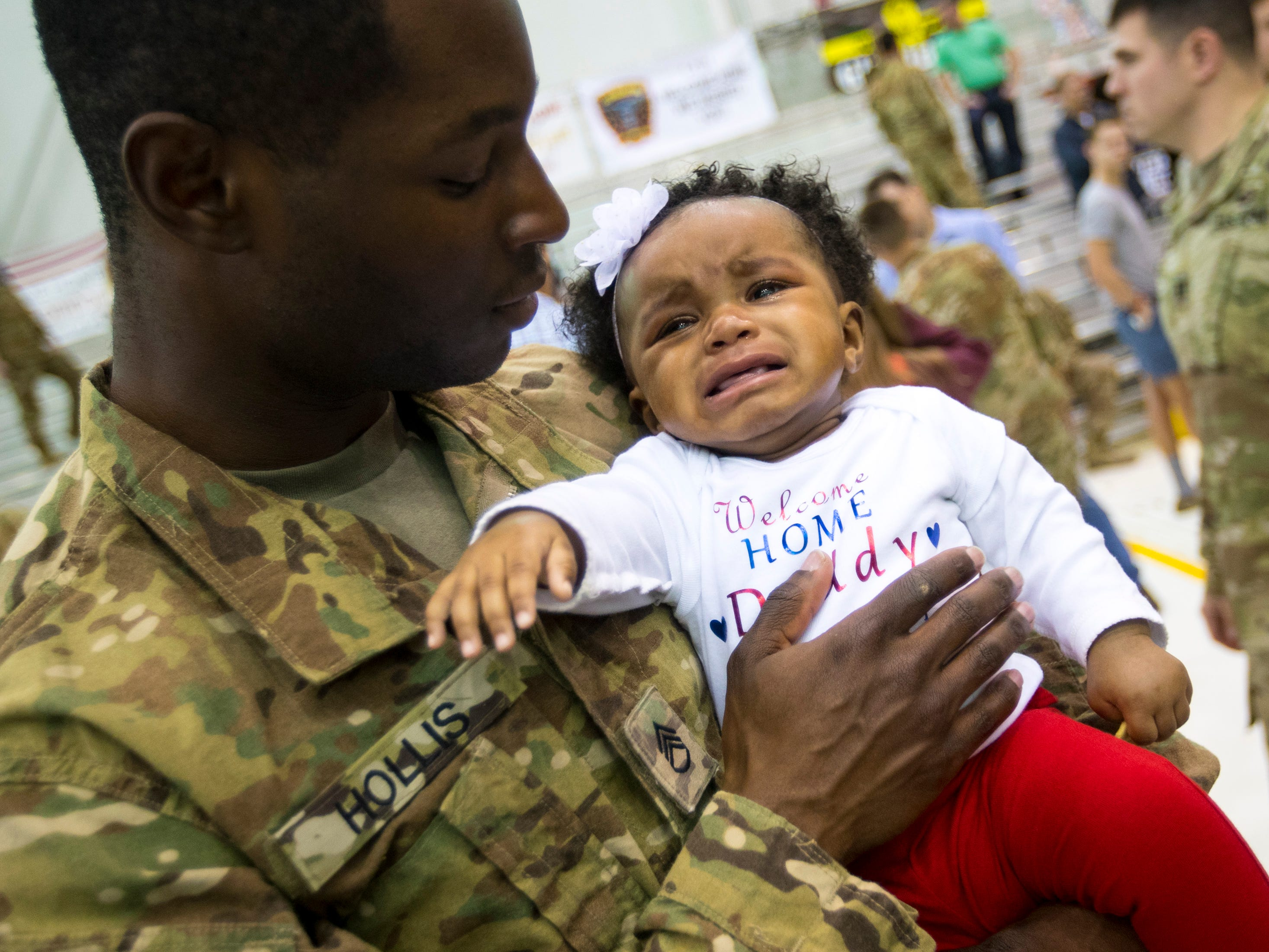 Aleighsia Hollis, 7 months, cries as her dad Wayne Hollis holds her for the first time during the welcome home ceremony for members of the 101st Combat Aviation Brigade at Fort Campbell in Clarksville on Tuesday, Feb. 5, 2019. The soldiers were returning from a nine-month deployment to Afghanistan.