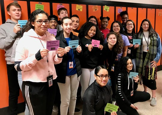 Students from one of Derrick Potts' world history classes showing the locker magnets they distributed to help raise awareness about human trafficking.