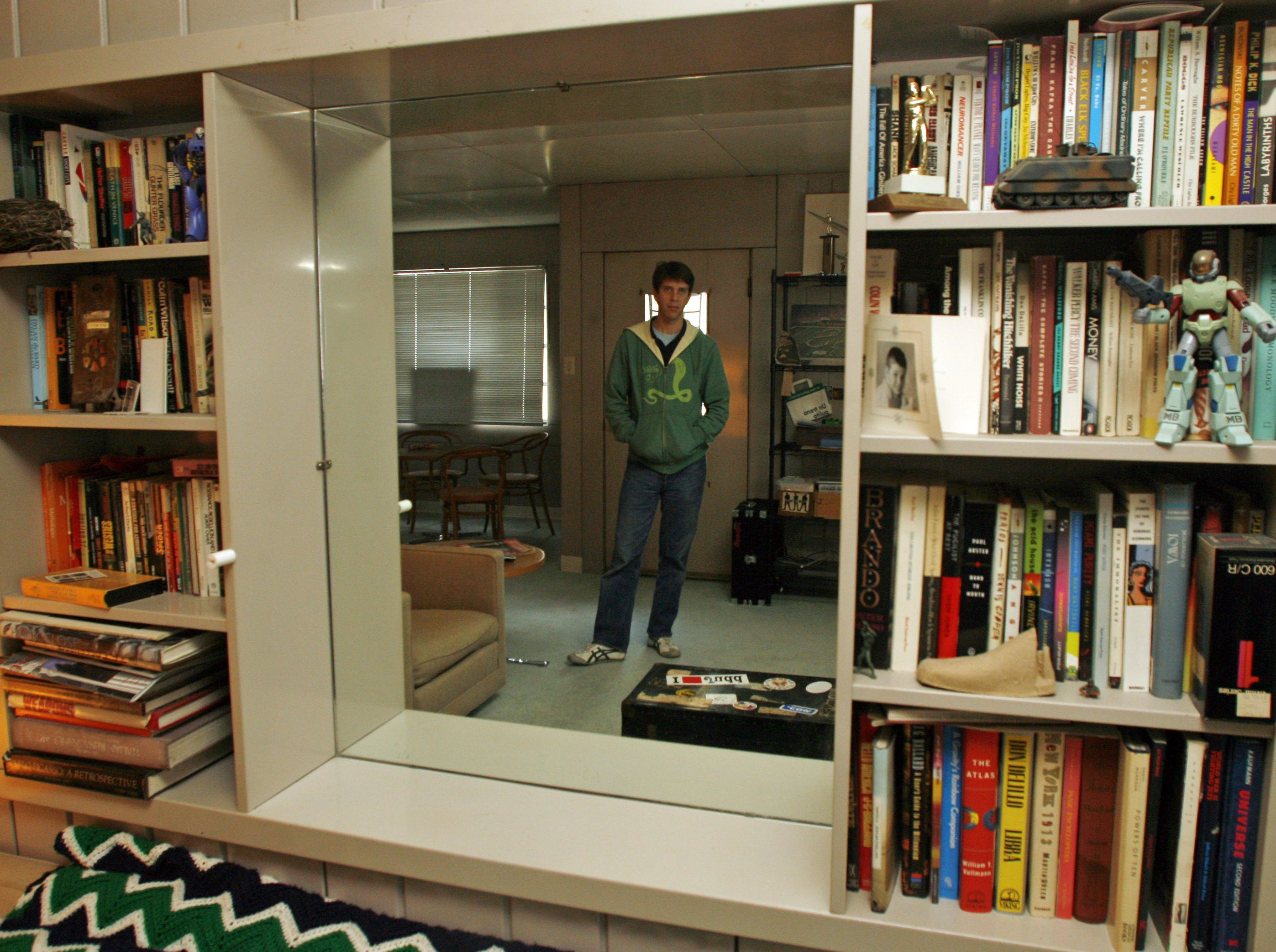 Alex Brown is reflected in the mirror between built-in bookshelves that are original to his Lustron home in this 2006 file photo.