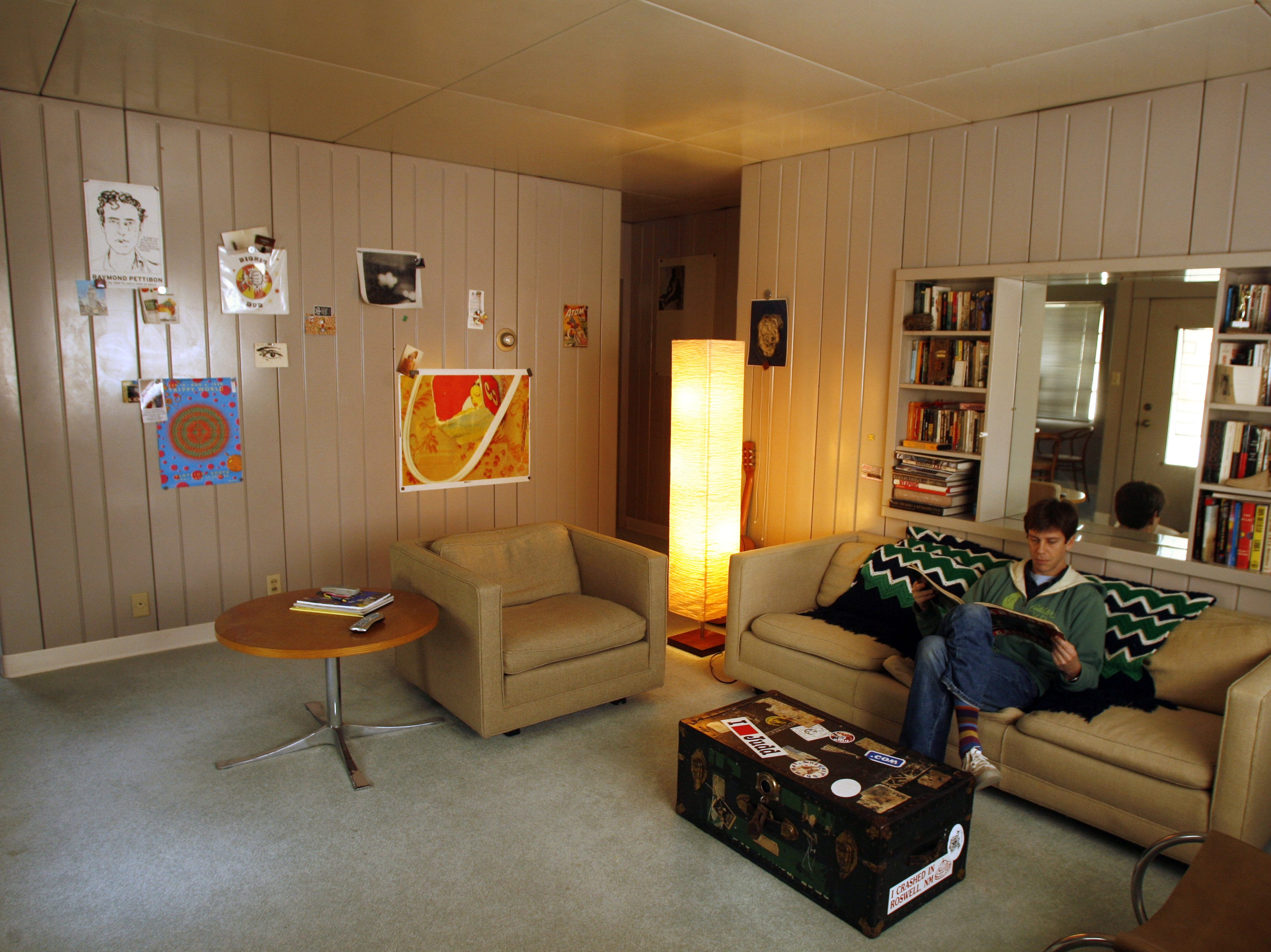 Alex Brown in his Lustron home in Des Moines from a 2006 file photo. He uses magnets to fasten art to the wall in his family room.