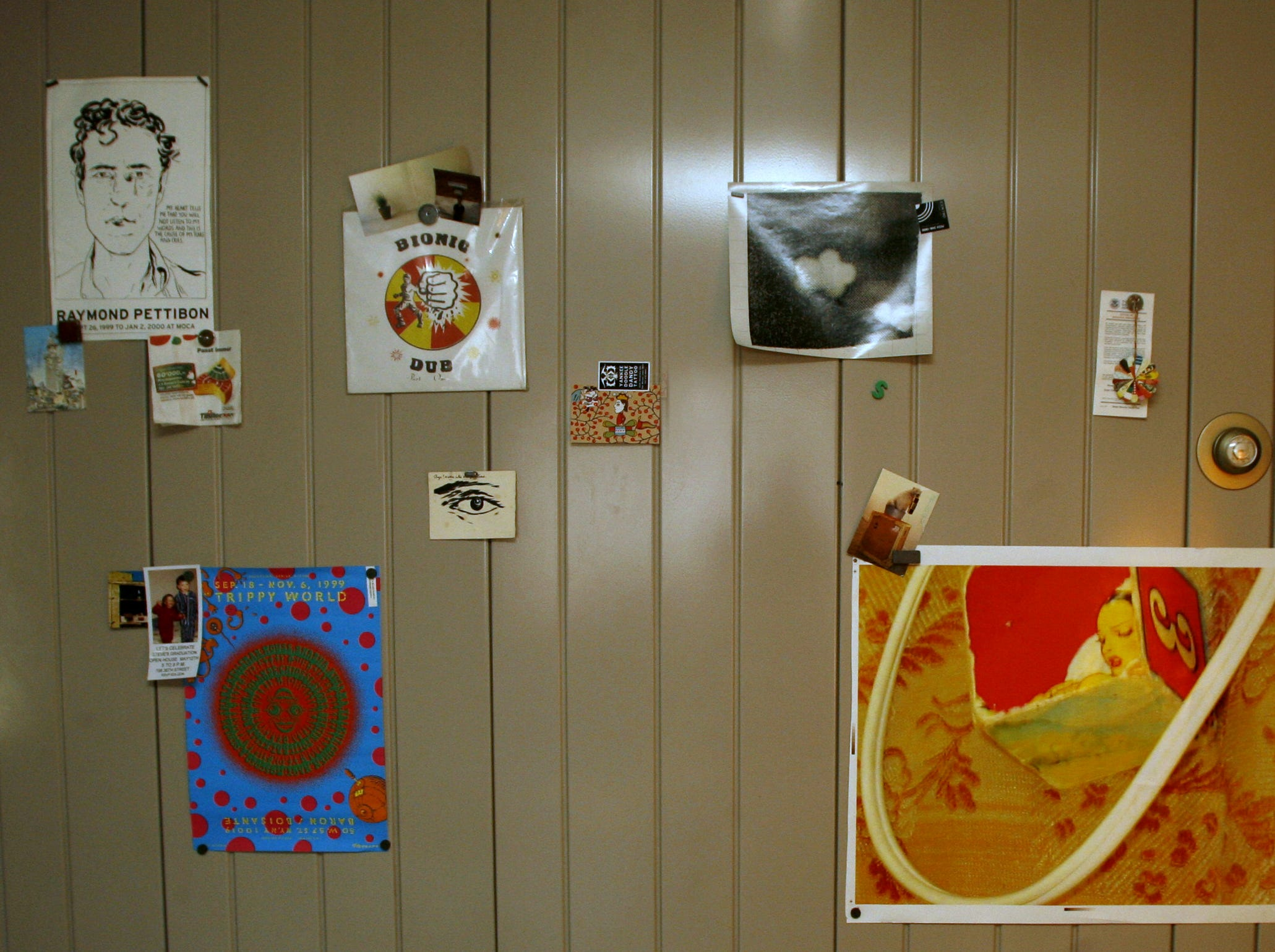 Alex Brown uses magnets to fasten artwork to his wall in his Lustron home in Des Moines in this 2006 file photo.