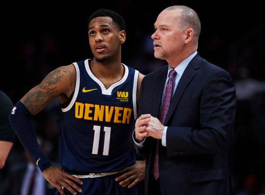 Nuggets coach Michael Malone talks to guard Monte Morris during the second half against the Pistons on Monday.