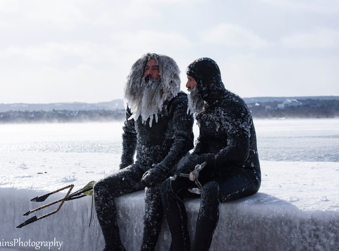 Surfers Allen Fina and Daniel Schetter pose for photos in Lake Superior during the polar vortex in January, 2019, in Marquette.