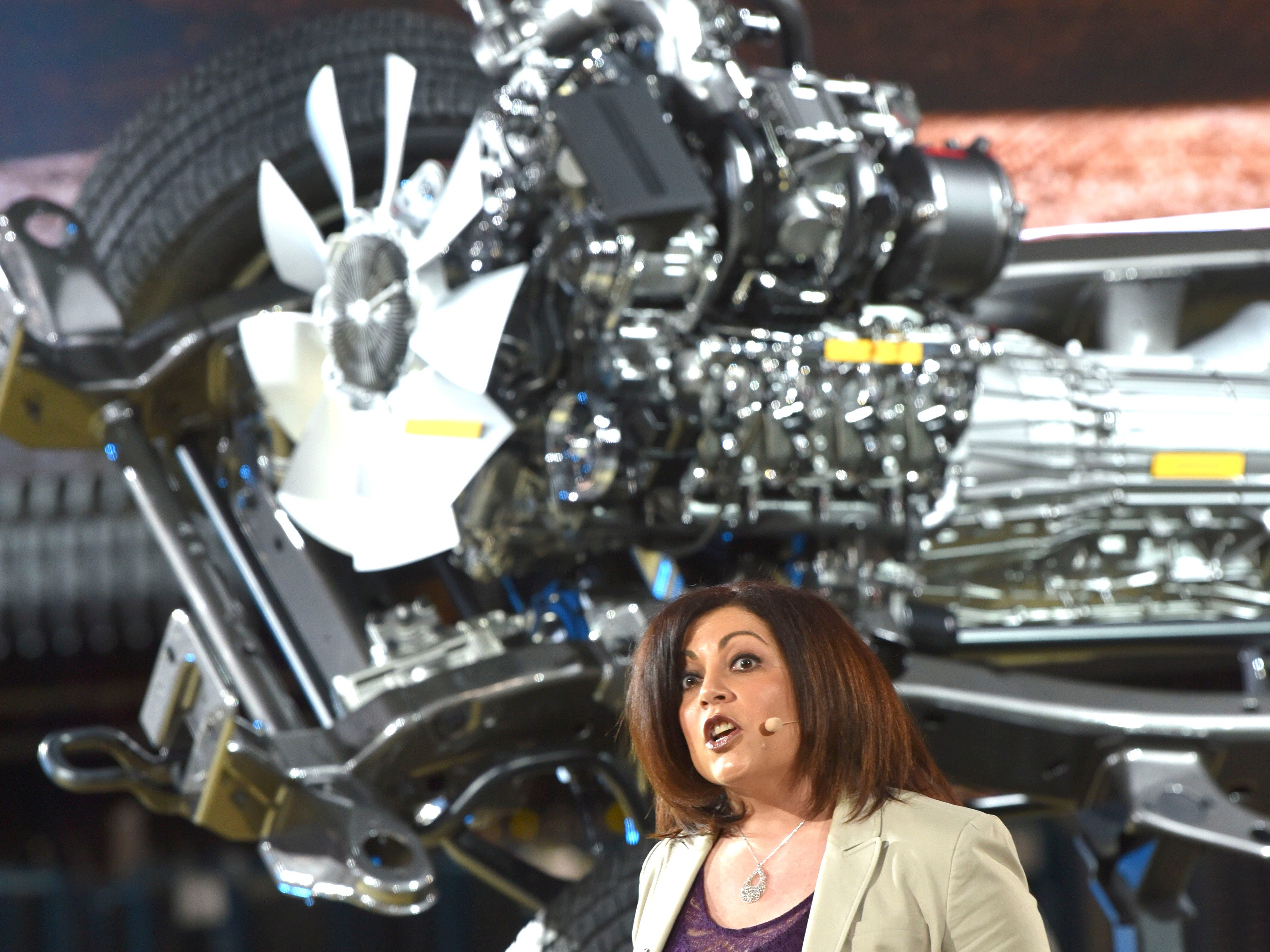 Jaclyn McQuaid, Chief Engineer of the Silverado HD, talks in front of an HD rolling chassis.  She said that Chevrolet has strengthened the heavy-duty trucks' axles, locking rear-differential, prop shaft and u-joint to allow the truck to use all 910-pounds-feet of torque in first gear.