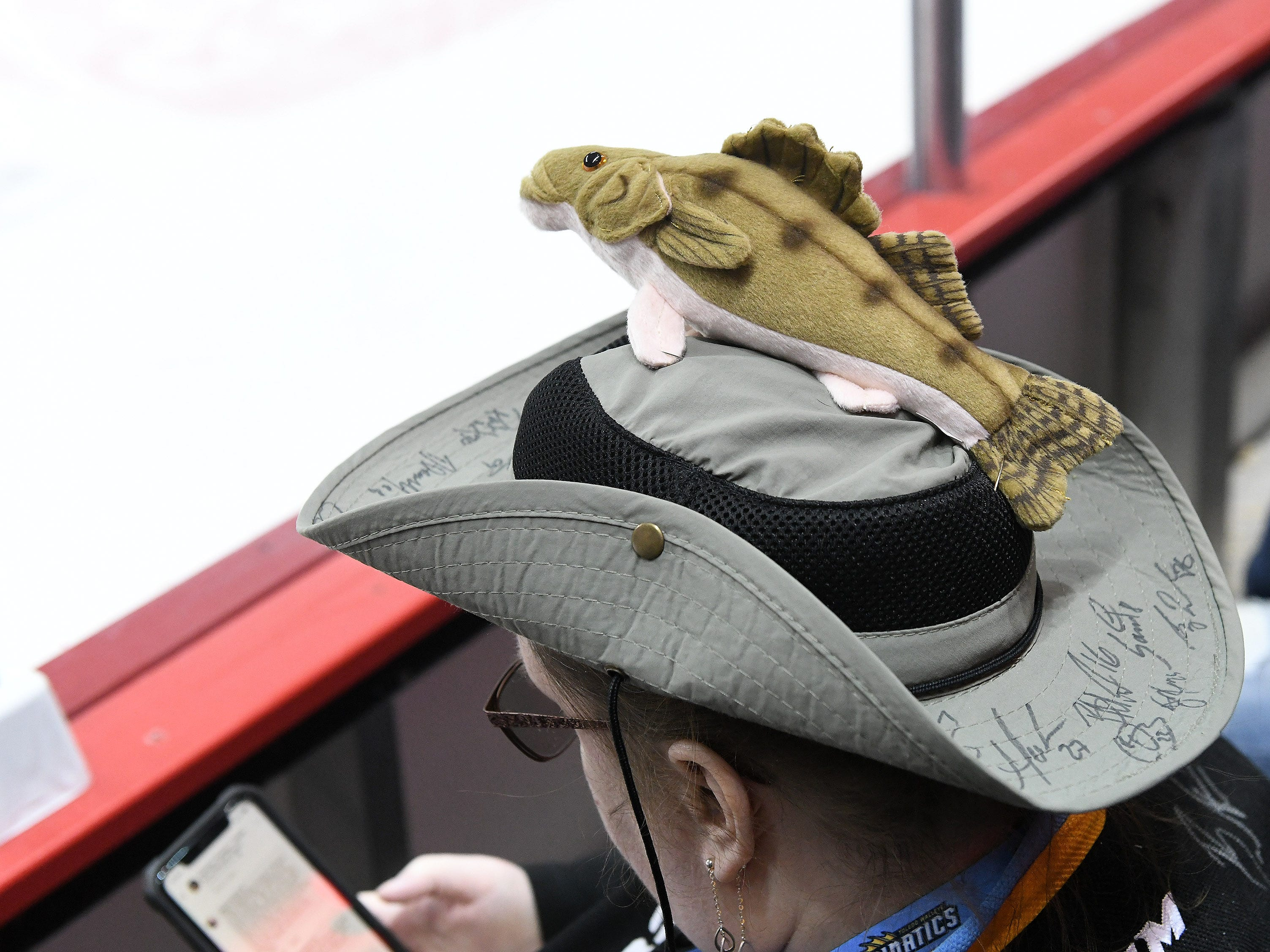 Tammy McInerney of Sylvania checks her phone during the second intermission.  She is wearing a hat that her husband, Michael, customized with a walleye pinned to the top. The hat is also covered with many player signatures.