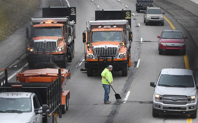 A Macomb County worker patches potholes on eastbound I-94, north of 8 Mile in St. Clair Shores, Tuesday.