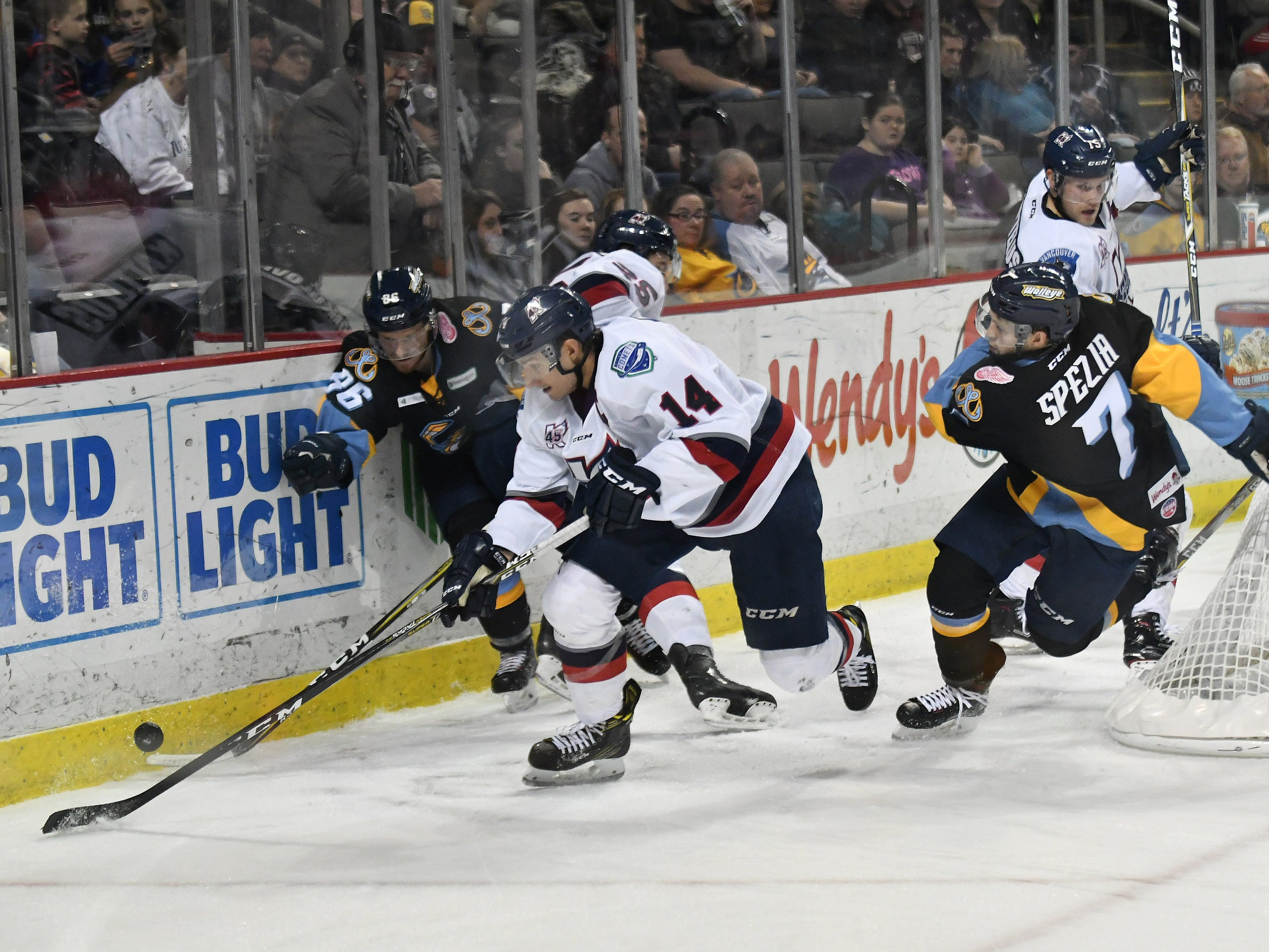 Kalamazoo defenseman Ben Wilson (14) tries to get to the puck while Toledo forward Greg Wolfe (86) battles Kalamazoo defenseman Aleksandr Mikulovich in the second period.  At right is Toledo forward Tyler Spezia (7).