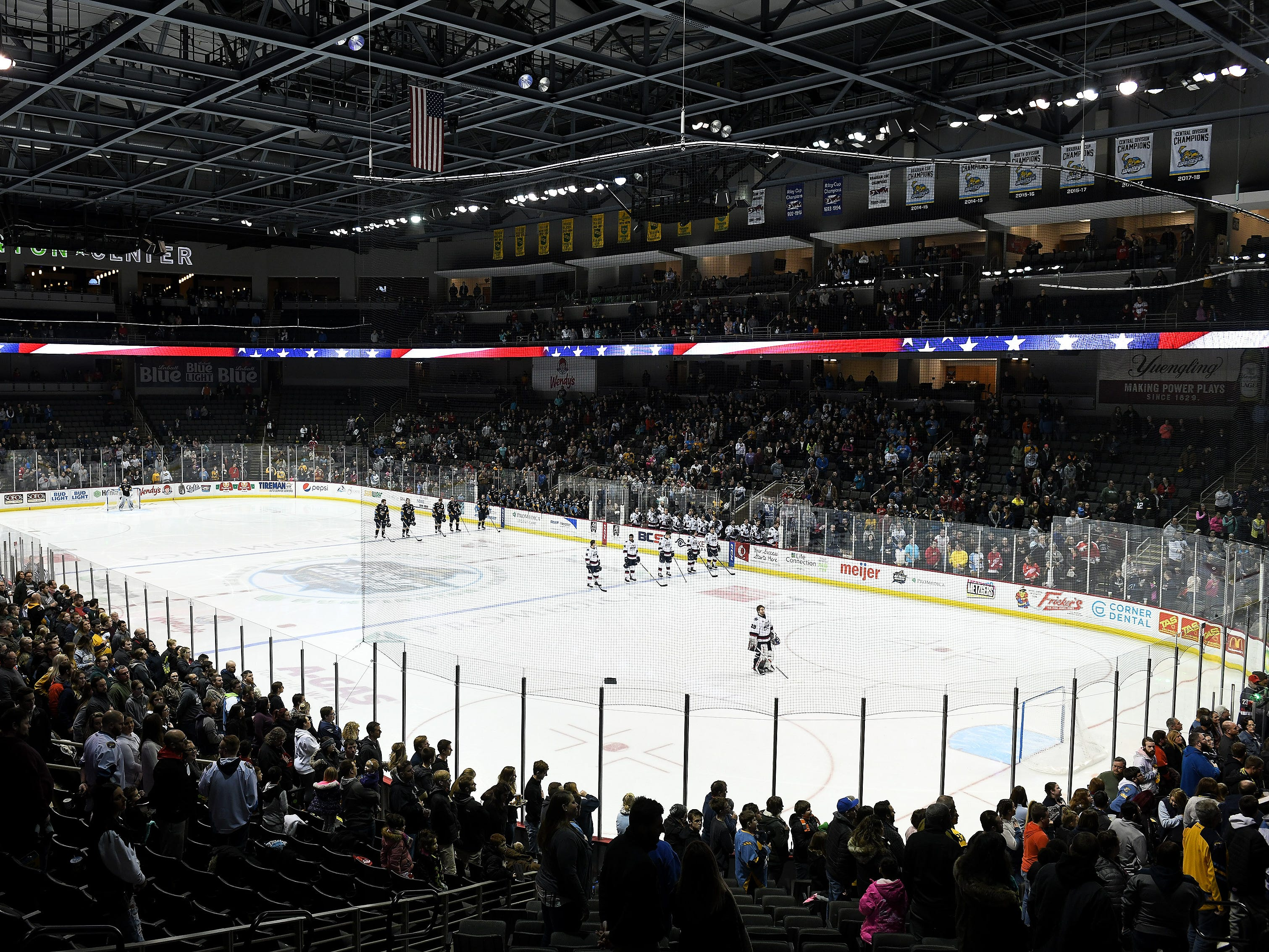 Players and fans stand for the national anthem before a game Thursday, Jan. 31, 2019, between the Toledo Walleye and the Kalamazoo Wings at the Huntington Center in Toledo, Ohio.