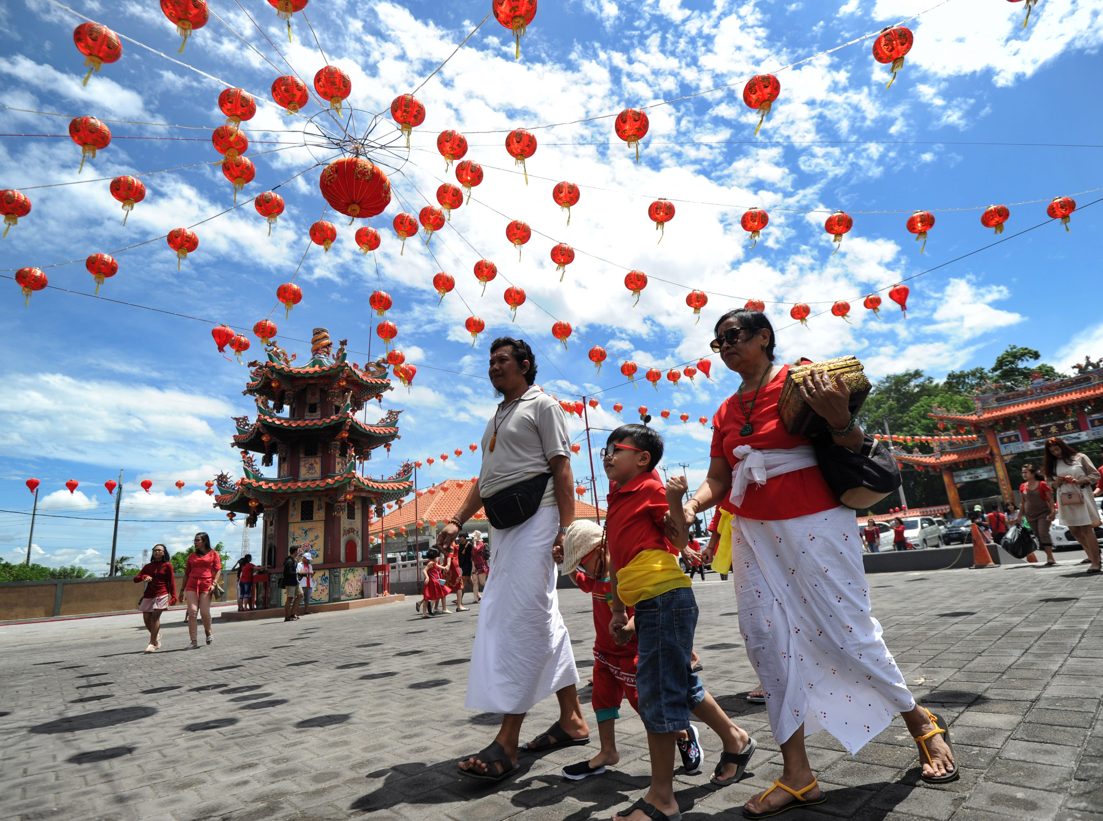 Balinese people wearing traditional outfits arrive at a Chinese temple to pray on the first day of the Lunar New Year in Denpasar on February 5, 2019.