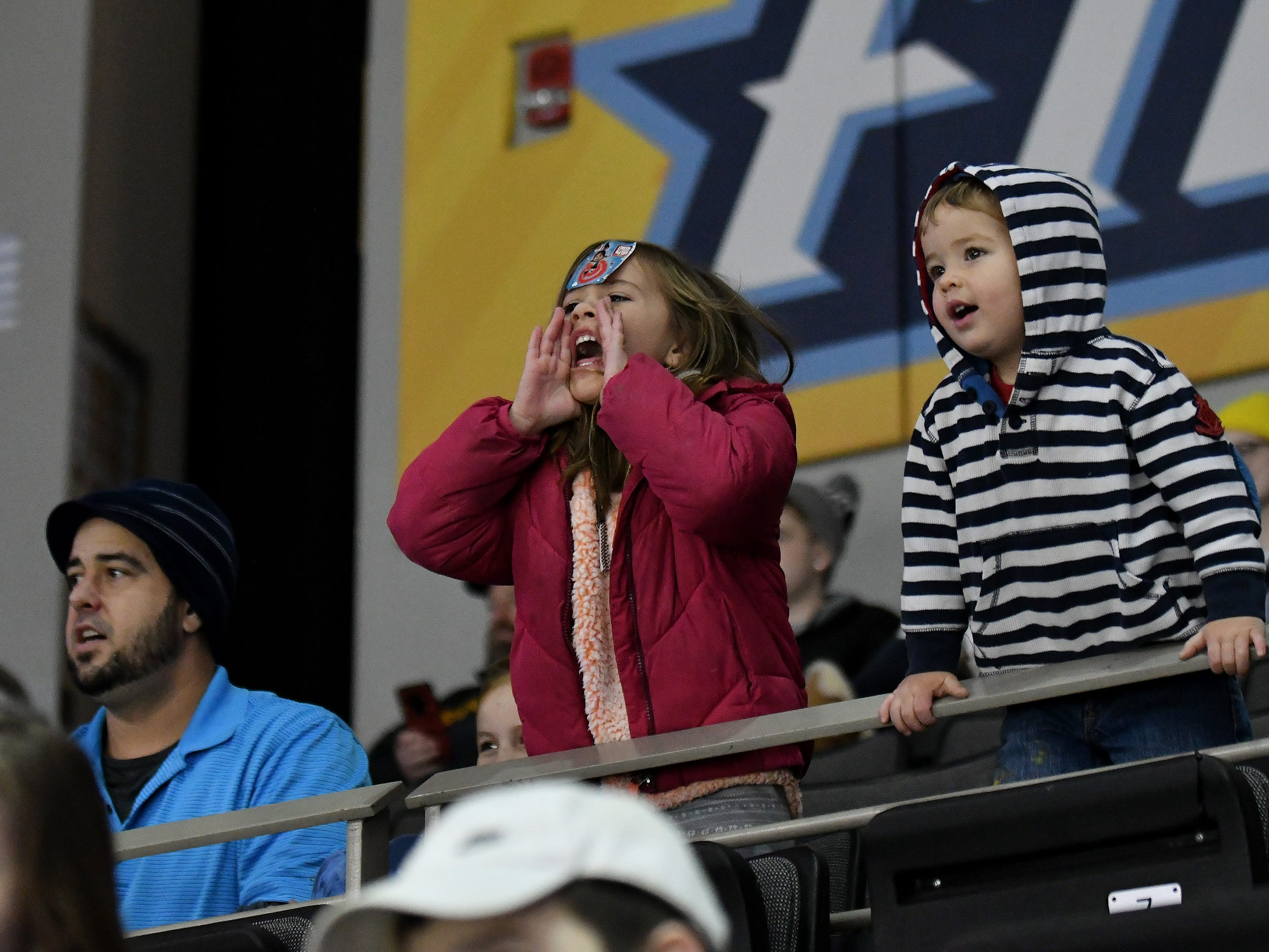 From left, Leila Okenka, 5, center, cheers for the Walleye next to her brother, Kahlai Okenka, 2, right, and father, Dan Okenka, left, in the first period.