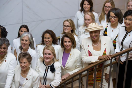 House Speaker Nancy Pelosi of Calif., center, is joined by other Congresswomen wearing white, as they pose for a group photo Tuesday before the State of the Union address by President Donald Trump, on Capitol Hill.