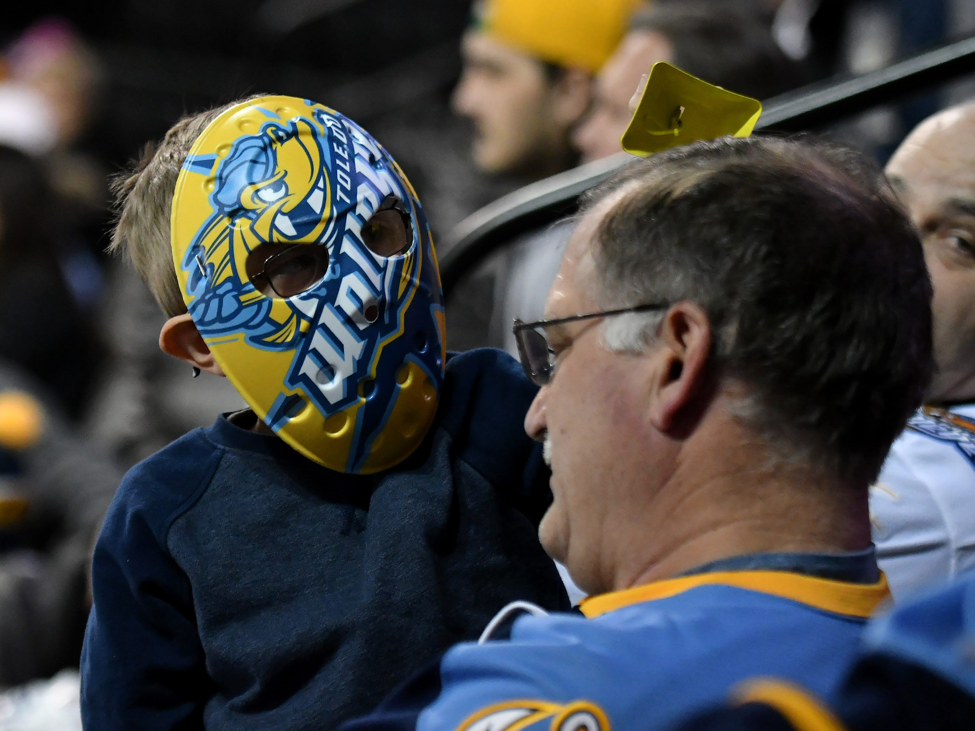 Attending his first game, Benjamin Havekost, 6, of Monroe rings a cowbell over the head of his grandfather, Brent Havekost in the third period.
