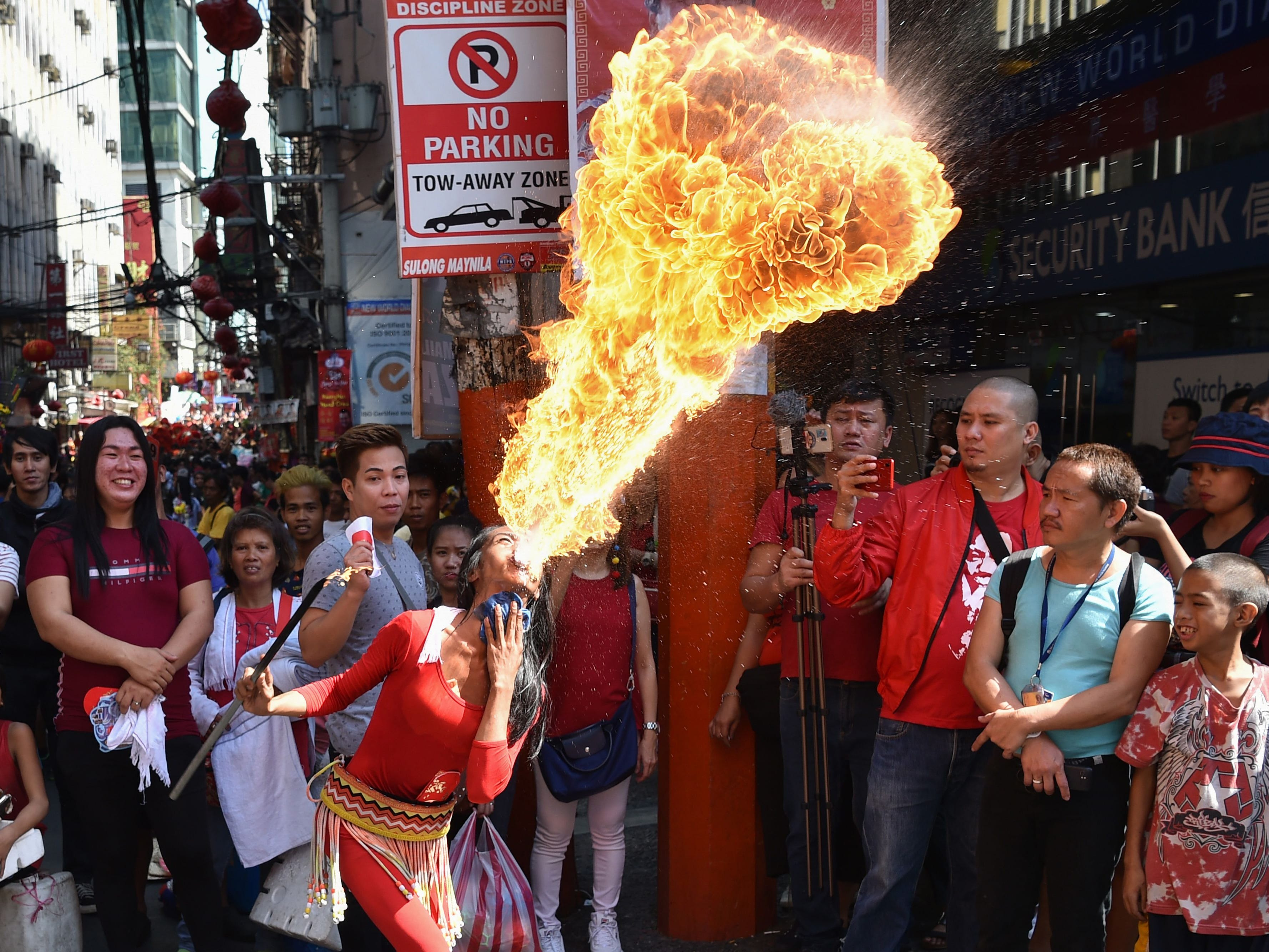 A fire breather performs during celebrations for the Lunar New Year of the Pig in Manila's Chinatown district on February 5, 2019.